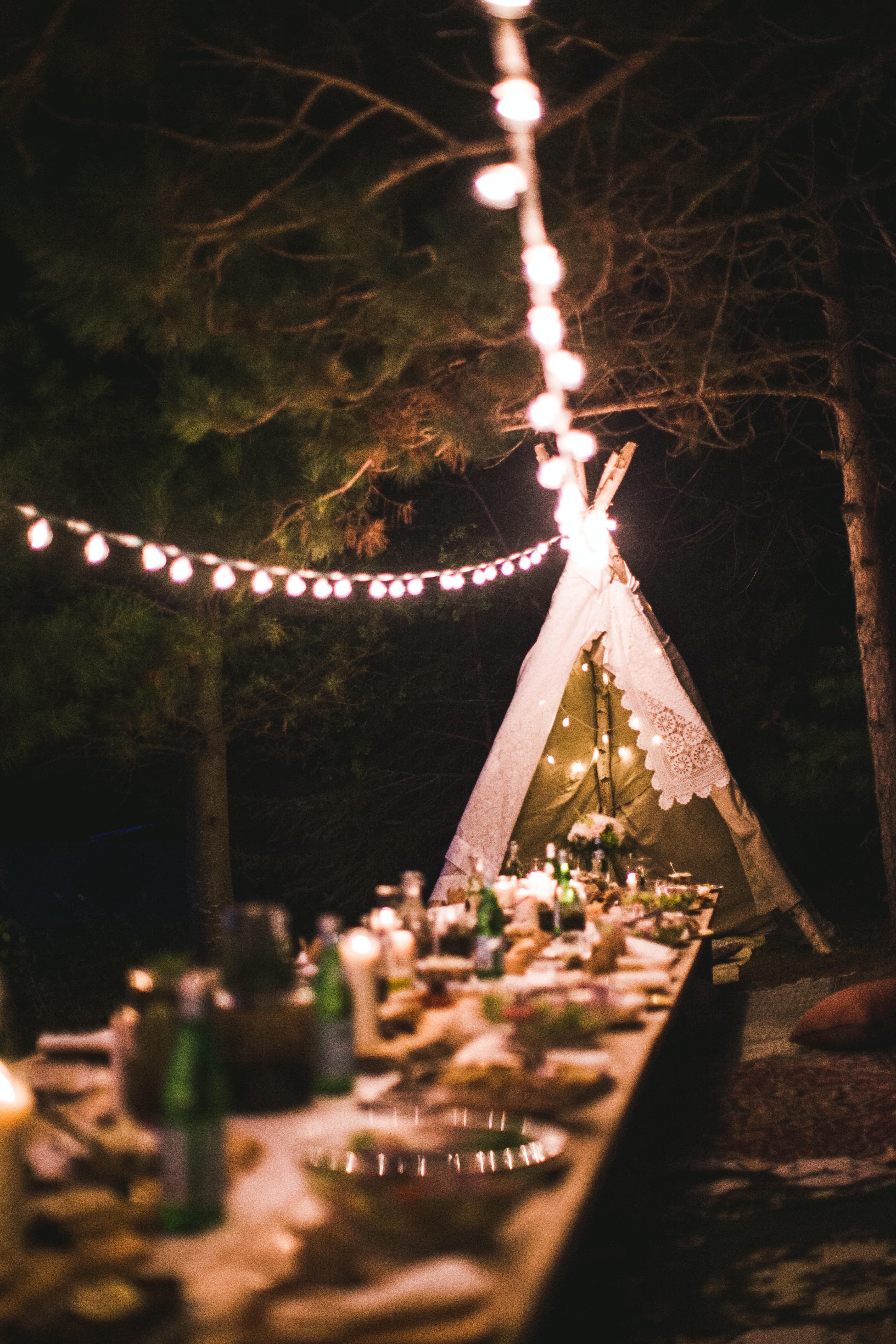 A large dinner table outside with special lighting.