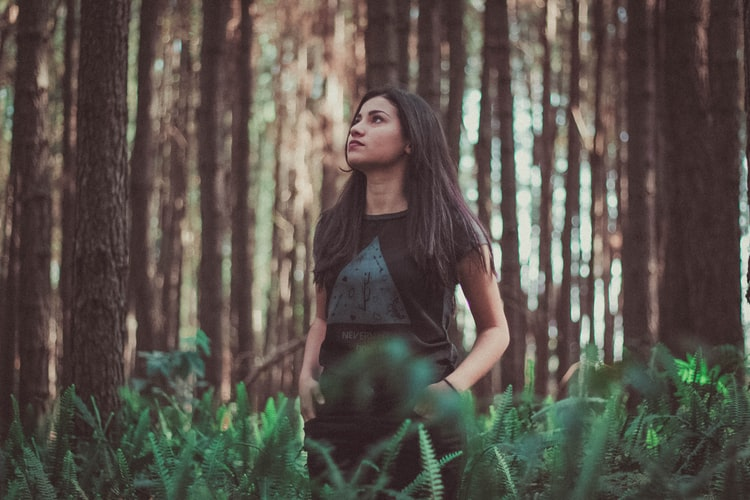 A woman with long dark hair standing in the middle of a forest, looking off to the side.