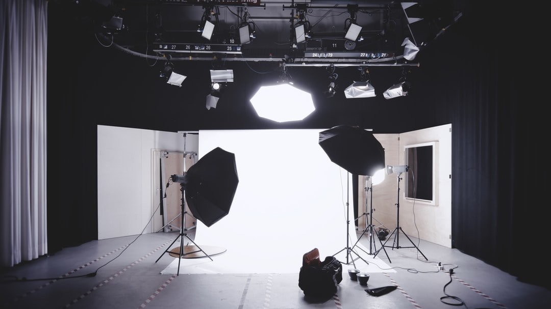 A photographic studio with a backdrop, lights, and softboxes