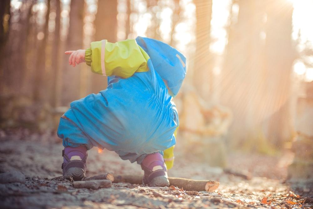 toddler picking up tree branch