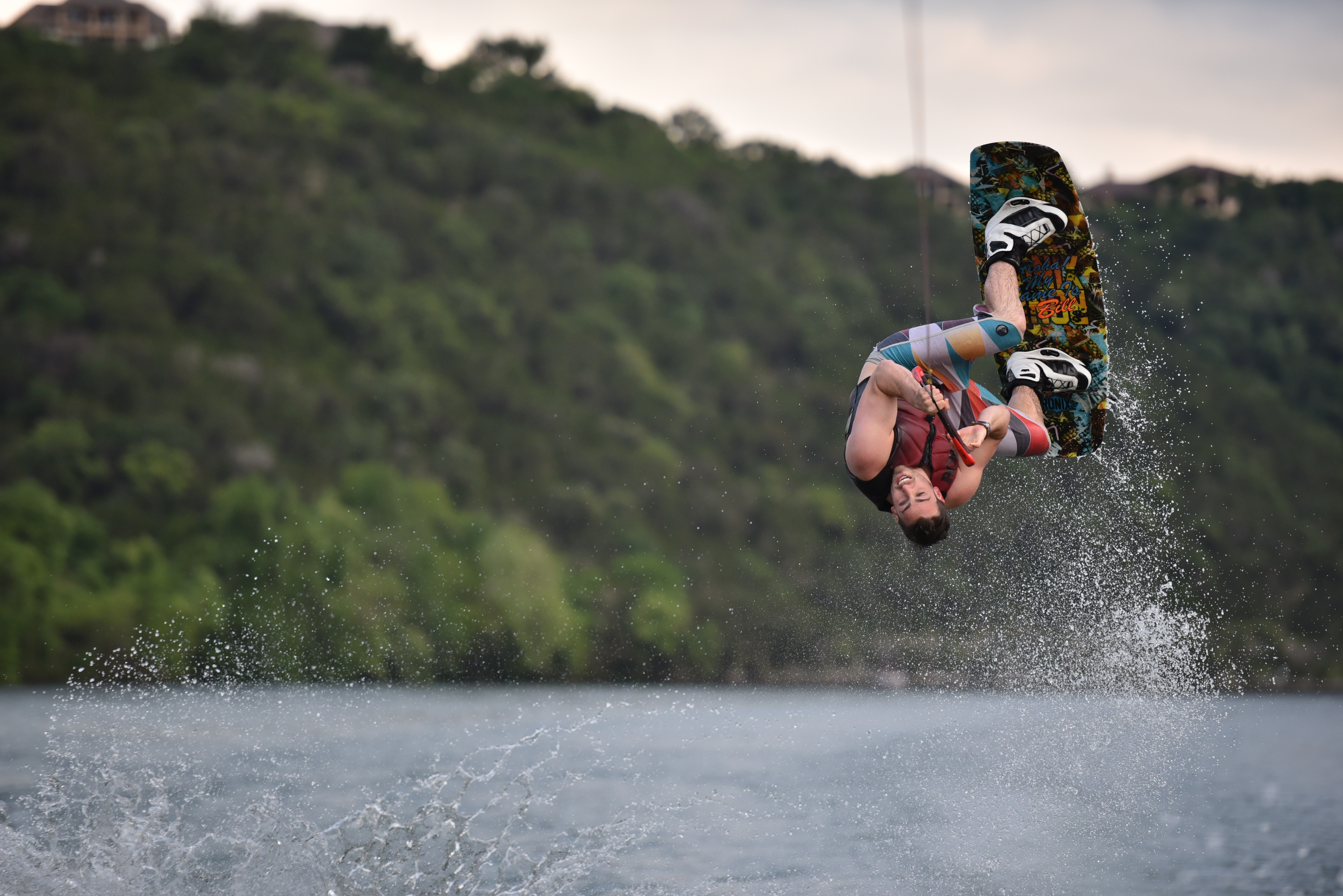 Wakeboarding athlete flipping up to the sky in Lake Austin