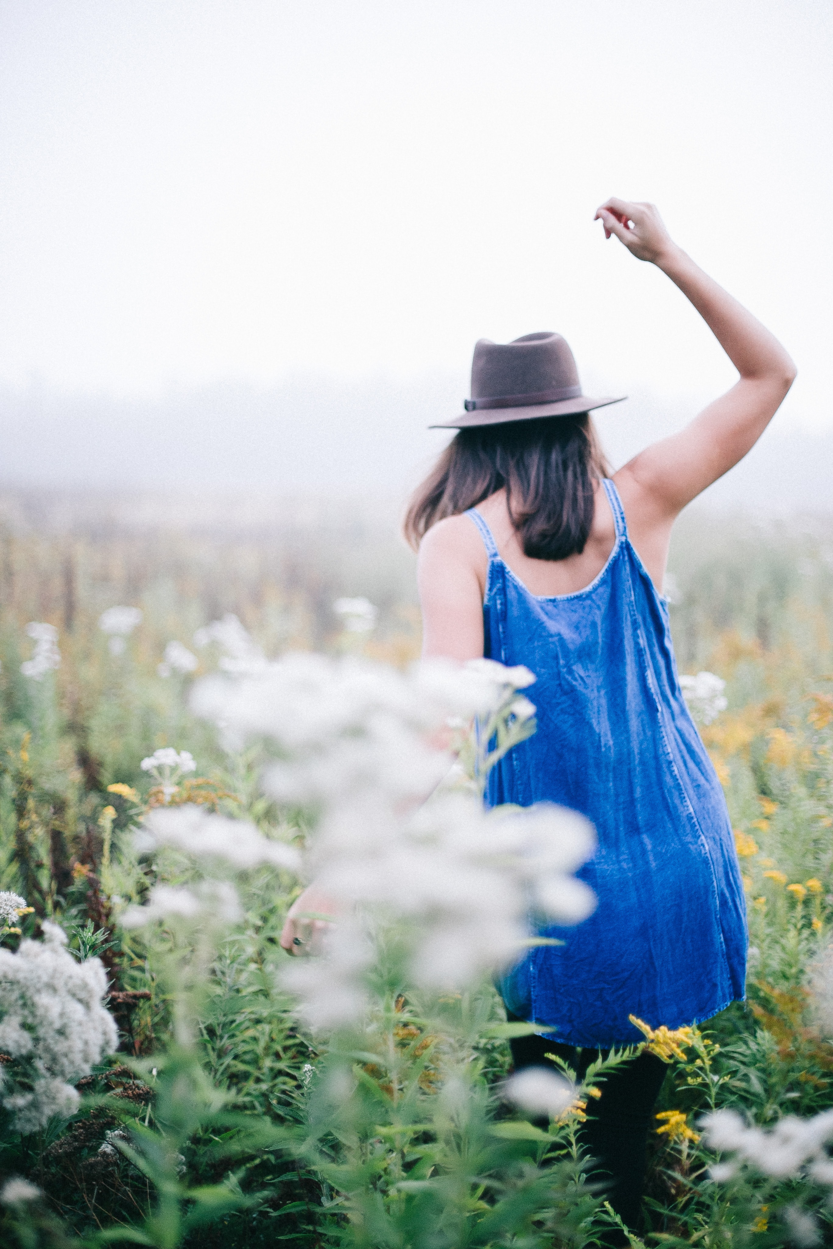 A girl wearing a hat and a blue dress walking in a meadow full of wildflowers