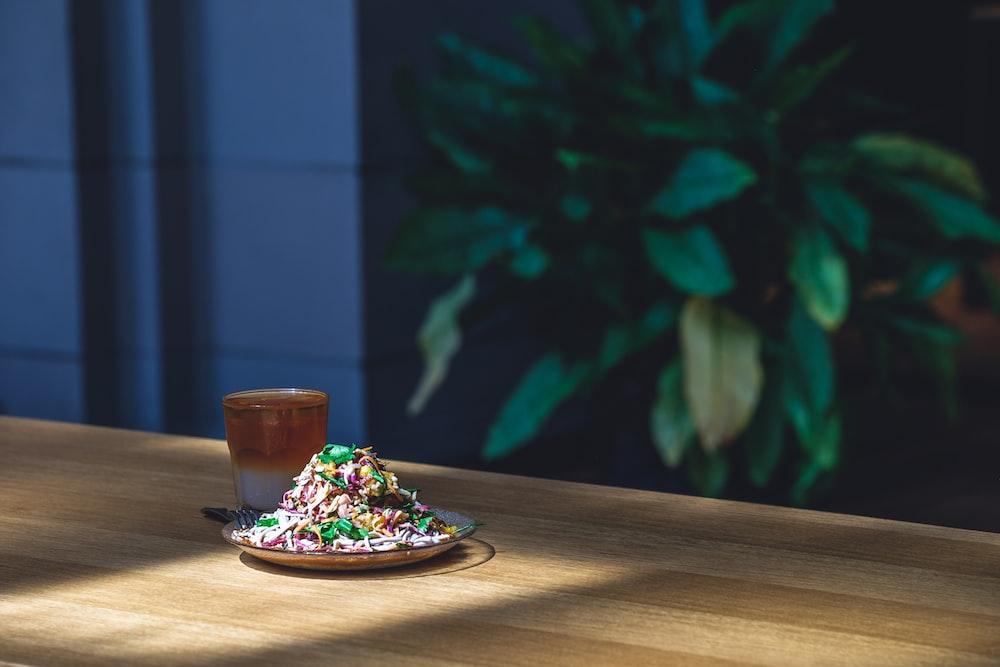 selective focus photography of dish on plate beside mug