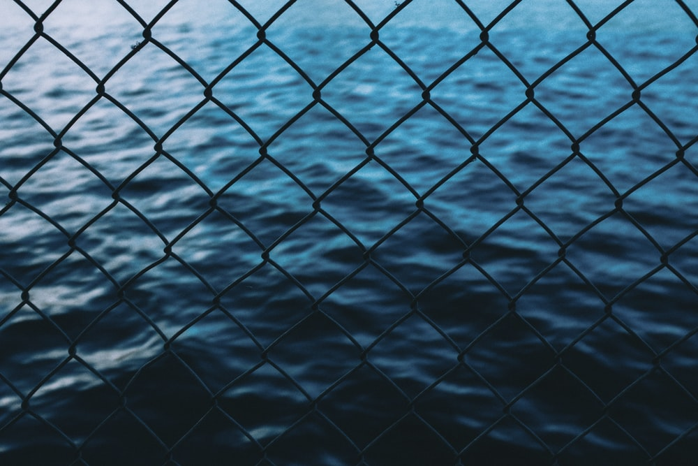 body of water in front of chain link fence