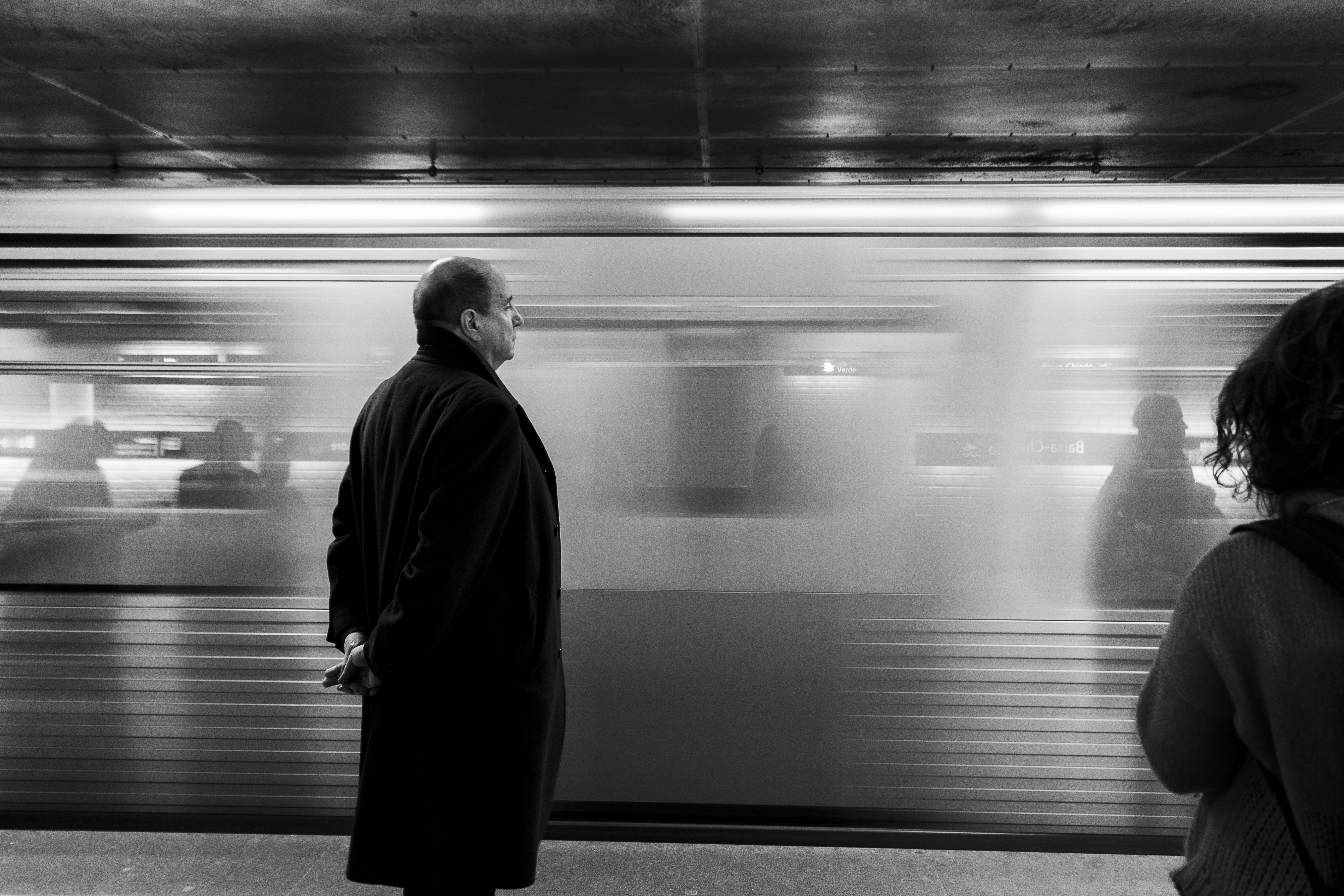 Black and white shot of bald man standing in coat on subway platform with moving train