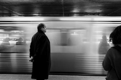 通過する電車を待つ人