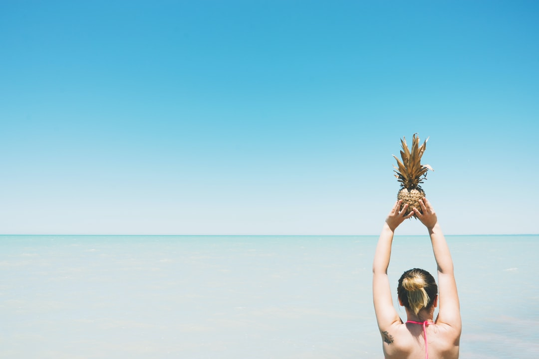 pineapple held up to sky by woman at beach