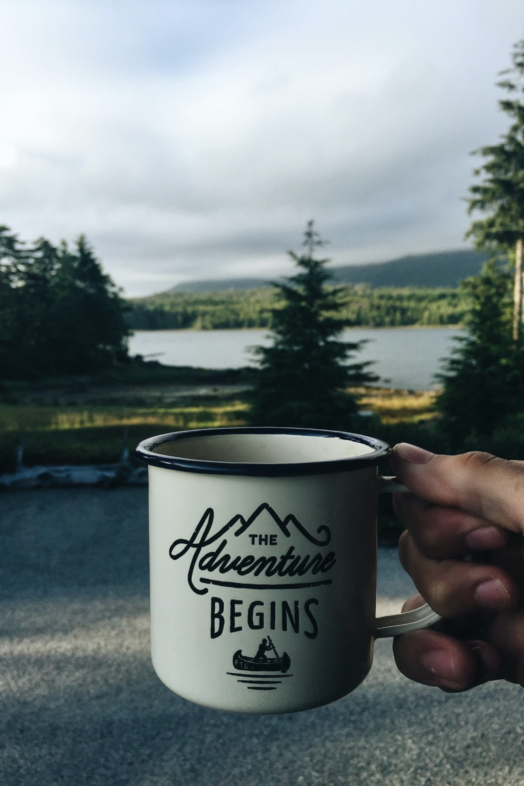 A hand holding a coffee mug in front of a road, pine trees, and river in Vancouver
