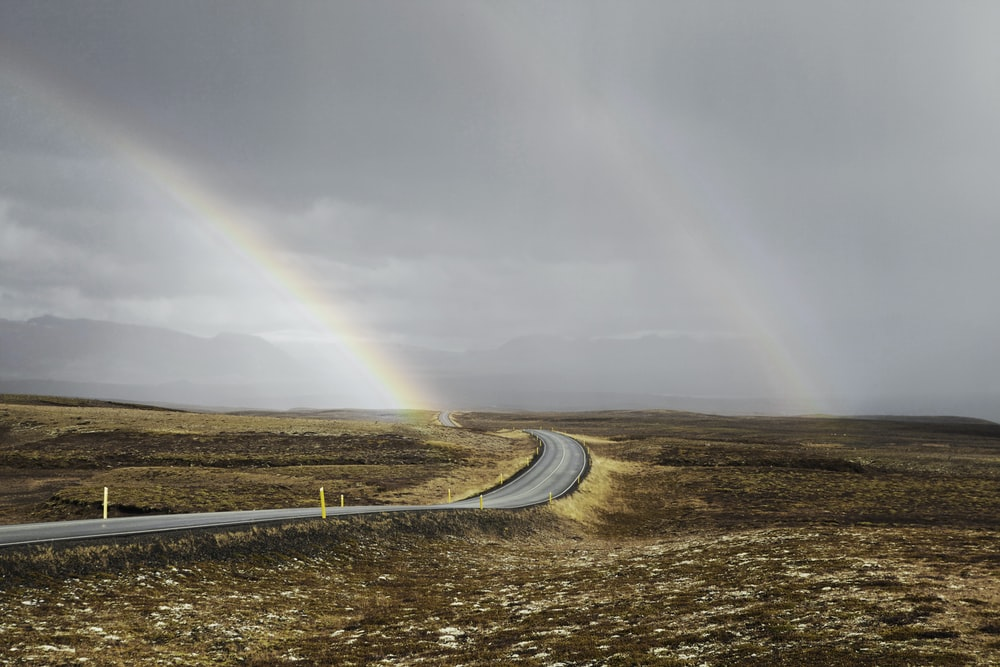 landscape photo of road under the rainbows
