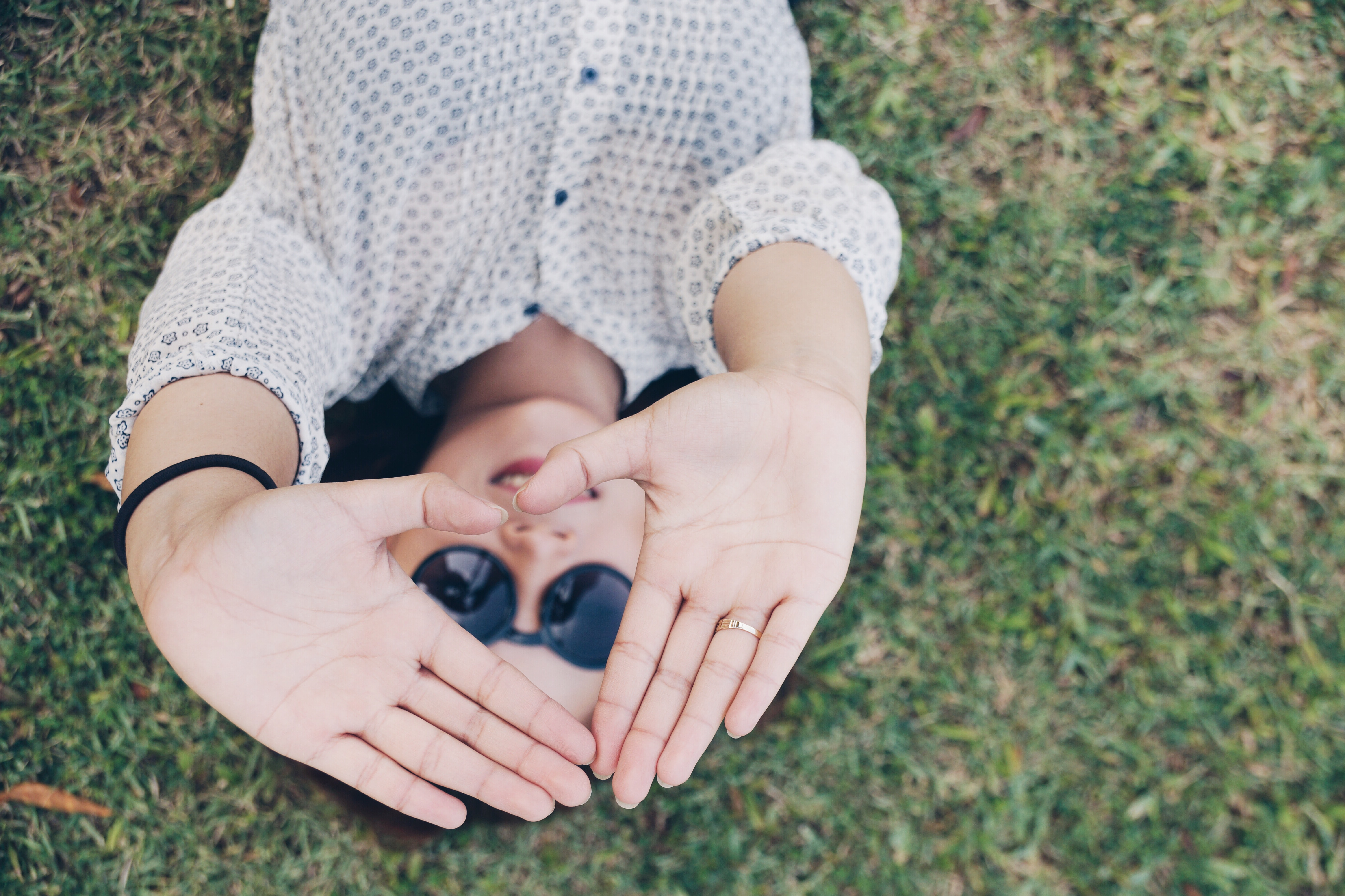 woman lying on grass forming her hands to triangle during daytime