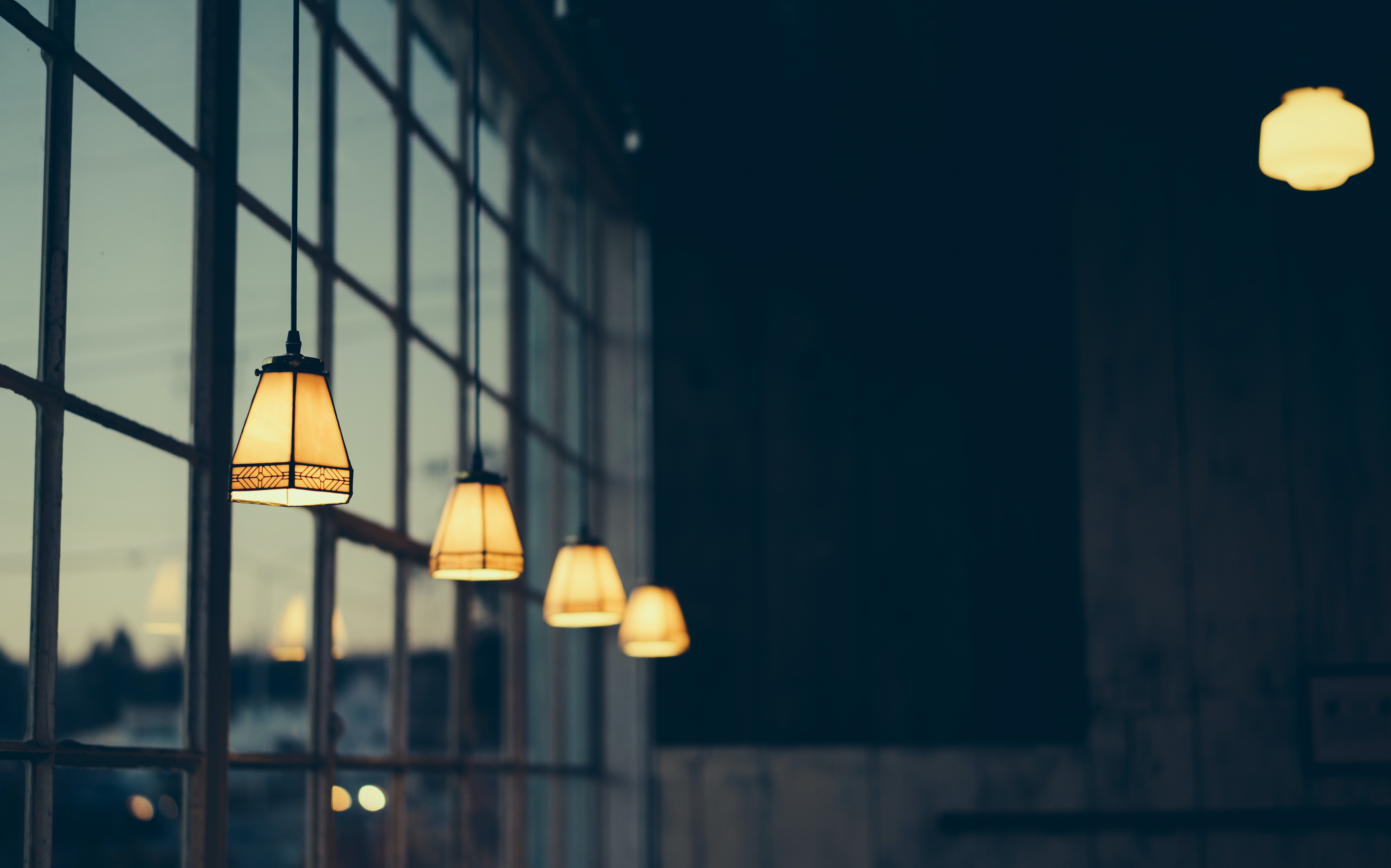 Lamps in yellow lampshades hanging from a ceiling near a window