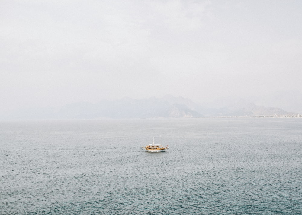 white boat sailing at the middle of the sea during daytime