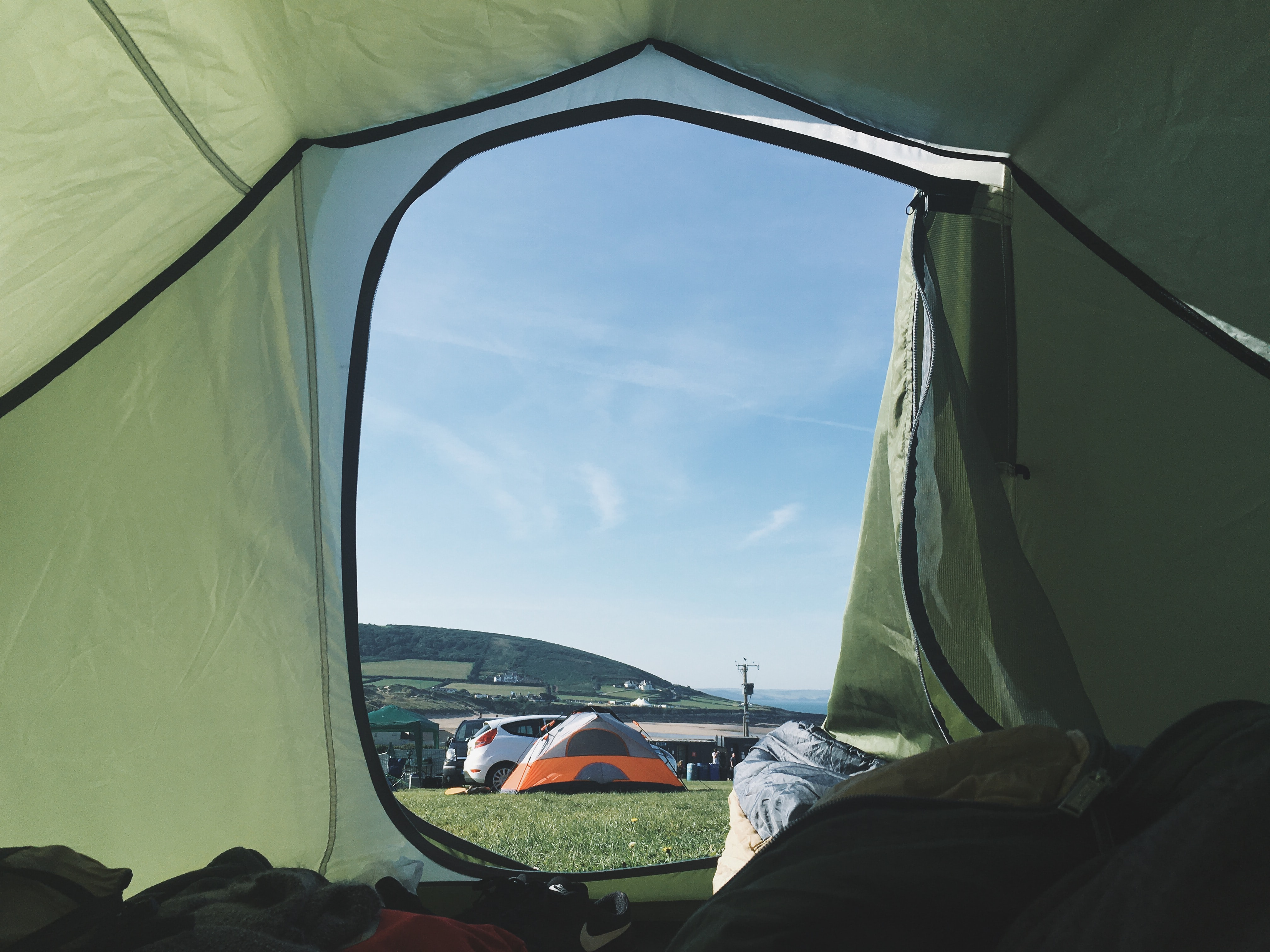 The view of a campsite and clear blue sky from inside of a green tent