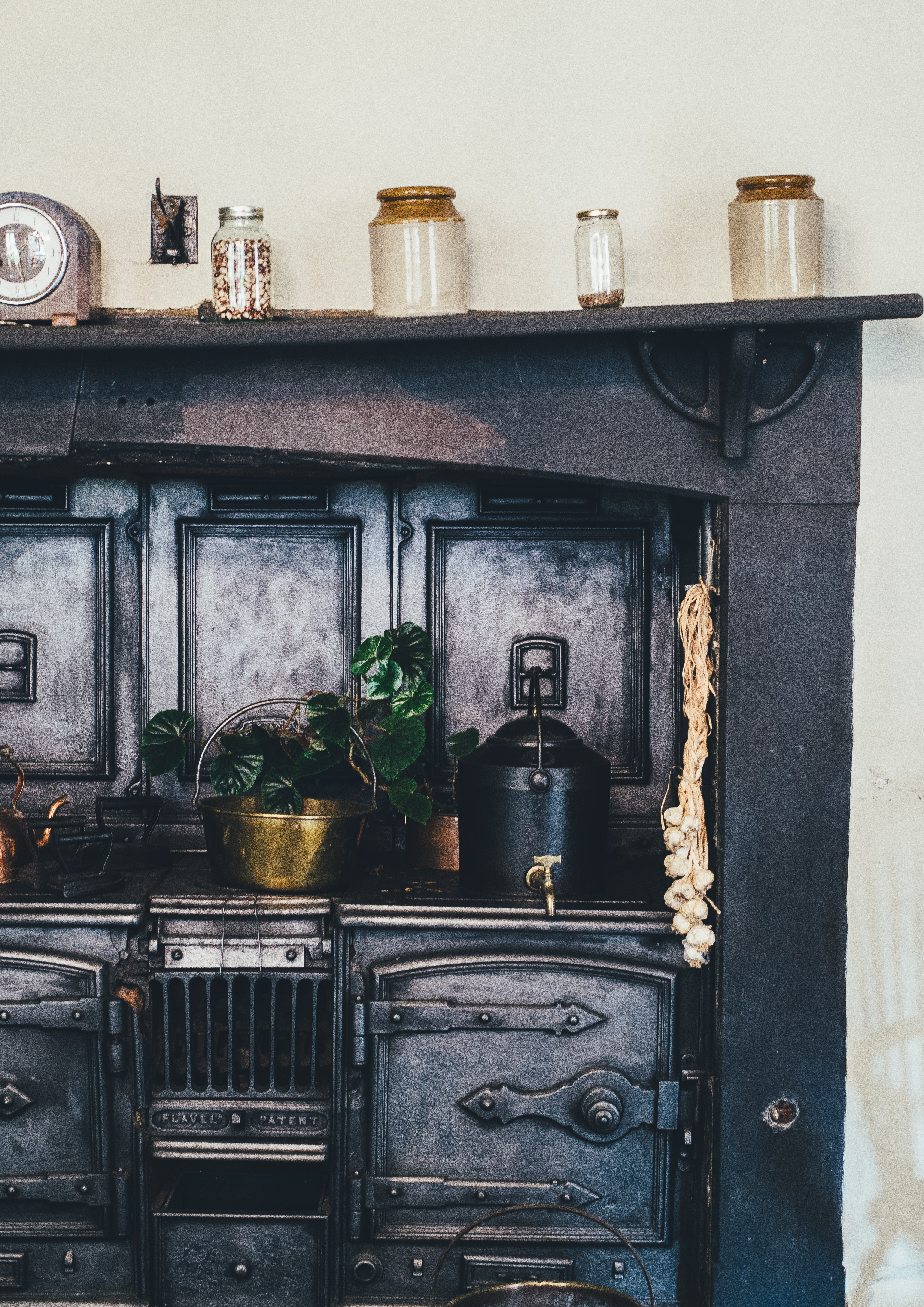 An old black kitchen shelf containing a stove, potted plant, jars, kettle and a clock.