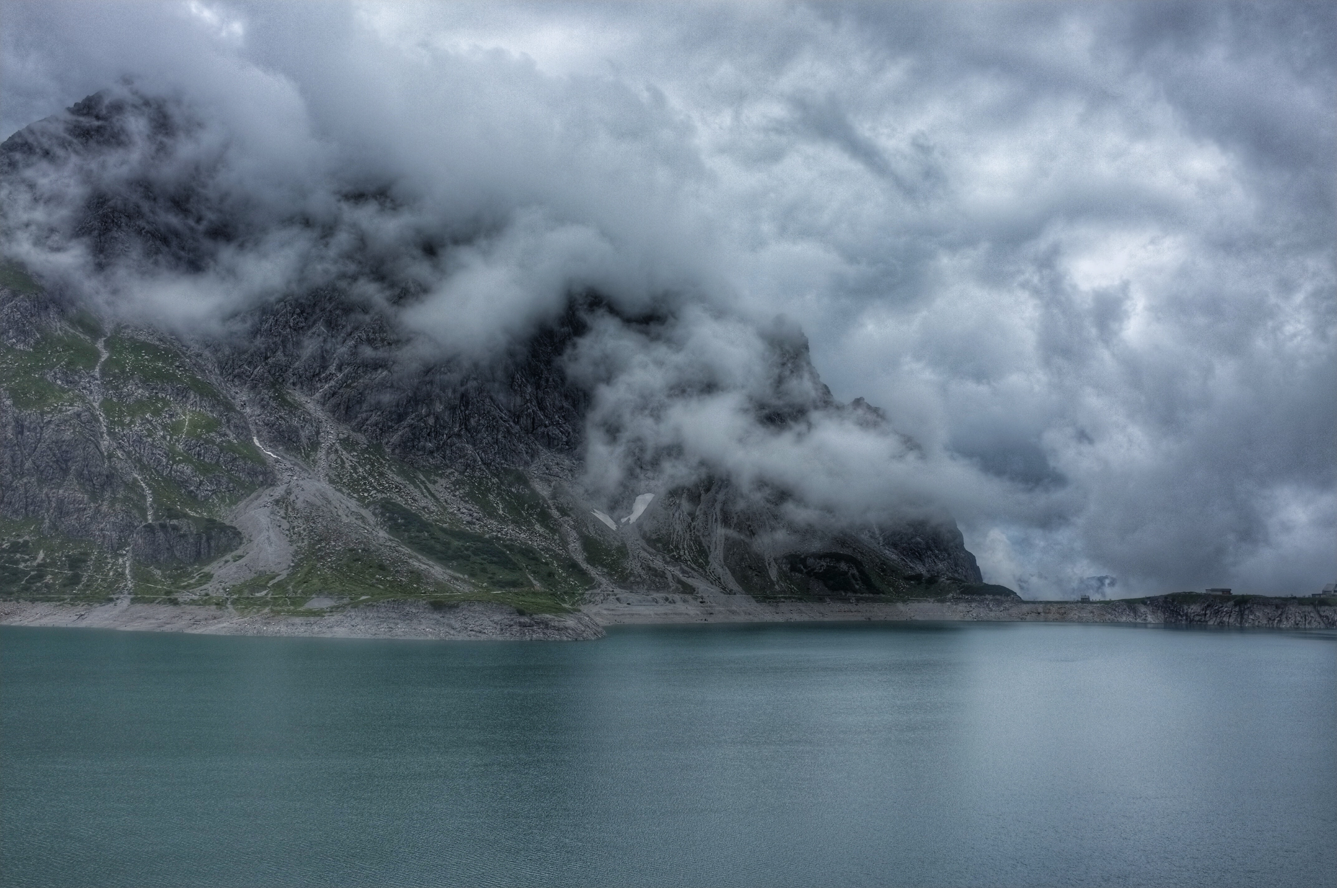 Fog rolls in on grassy mountains by a still lake in Lünersee