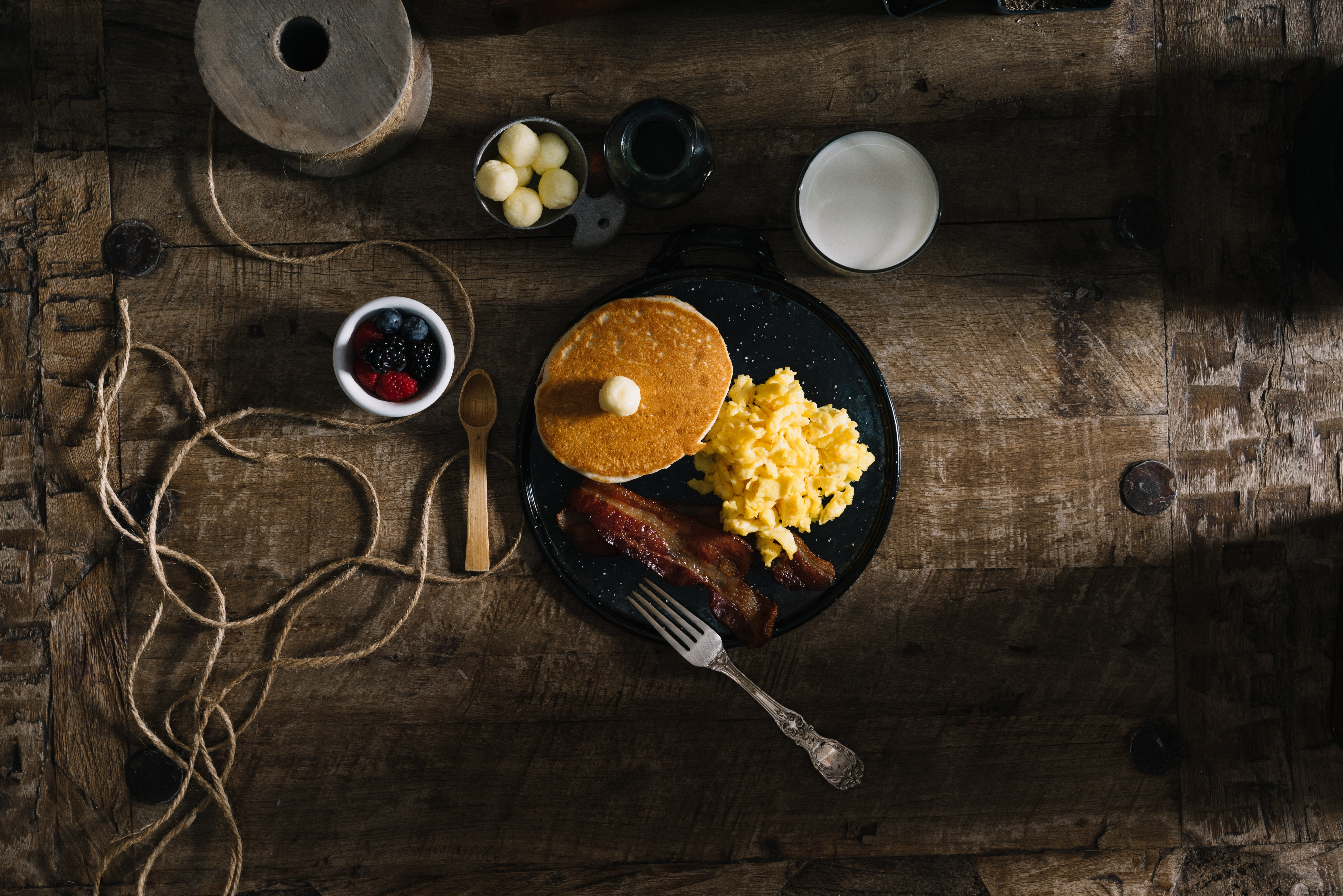 Rustic breakfast tablescape with pancakes, eggs, and bacon