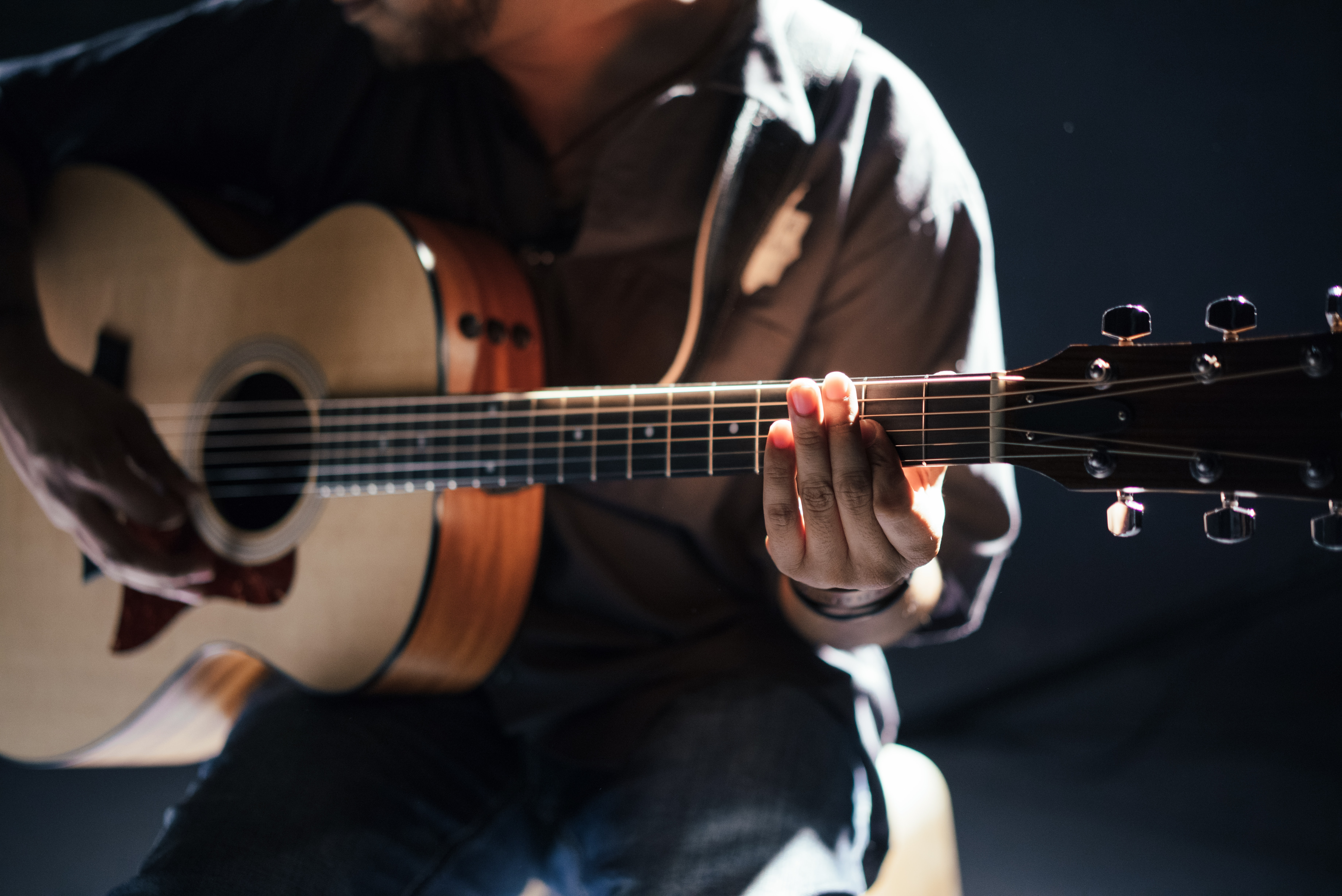A seated person playing acoustic guitar