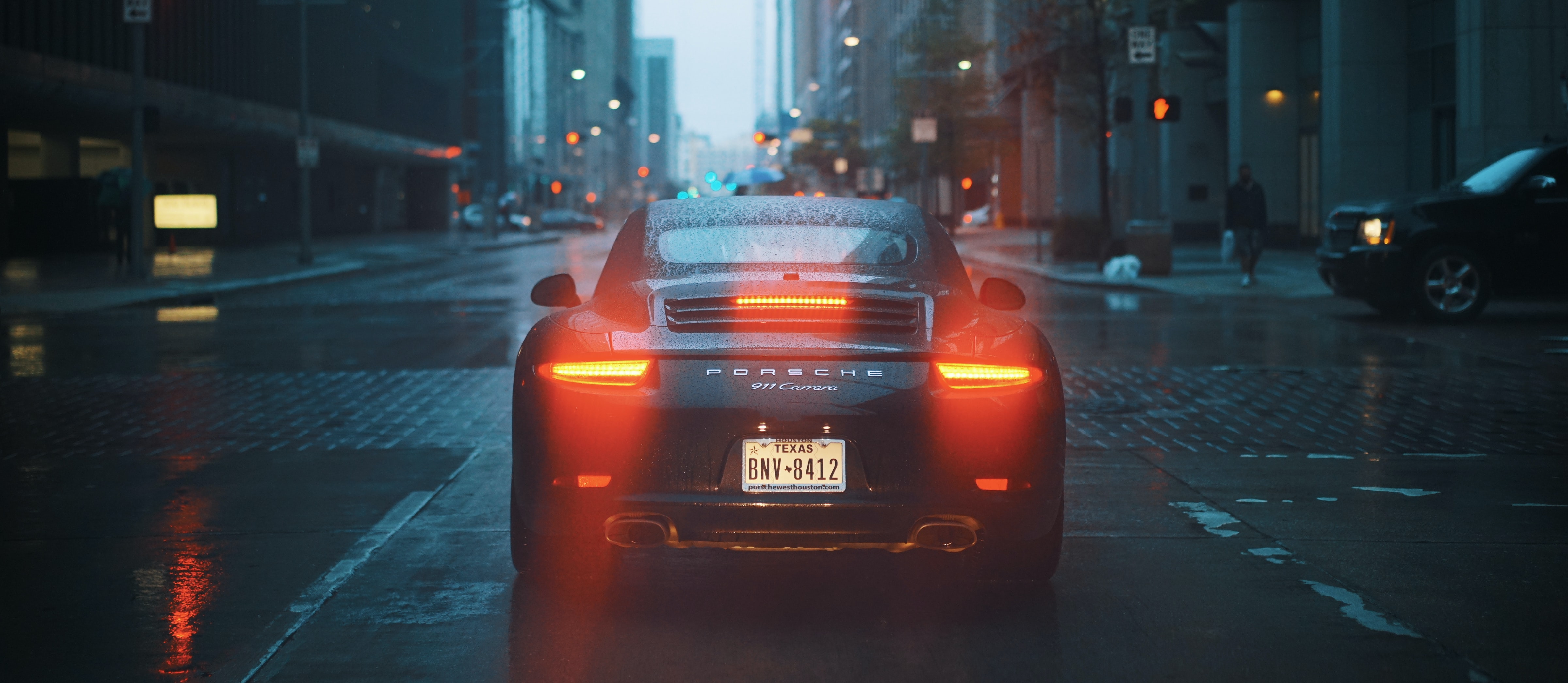 The back of a black Porsche 911 with its tail lights on on a wet street