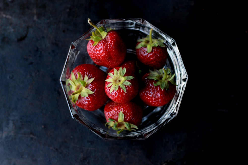 red strawberries in clear glass bowl