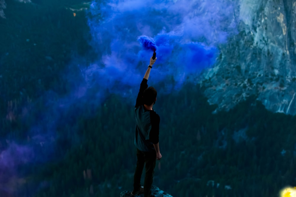 man holding blue powder while raising hand