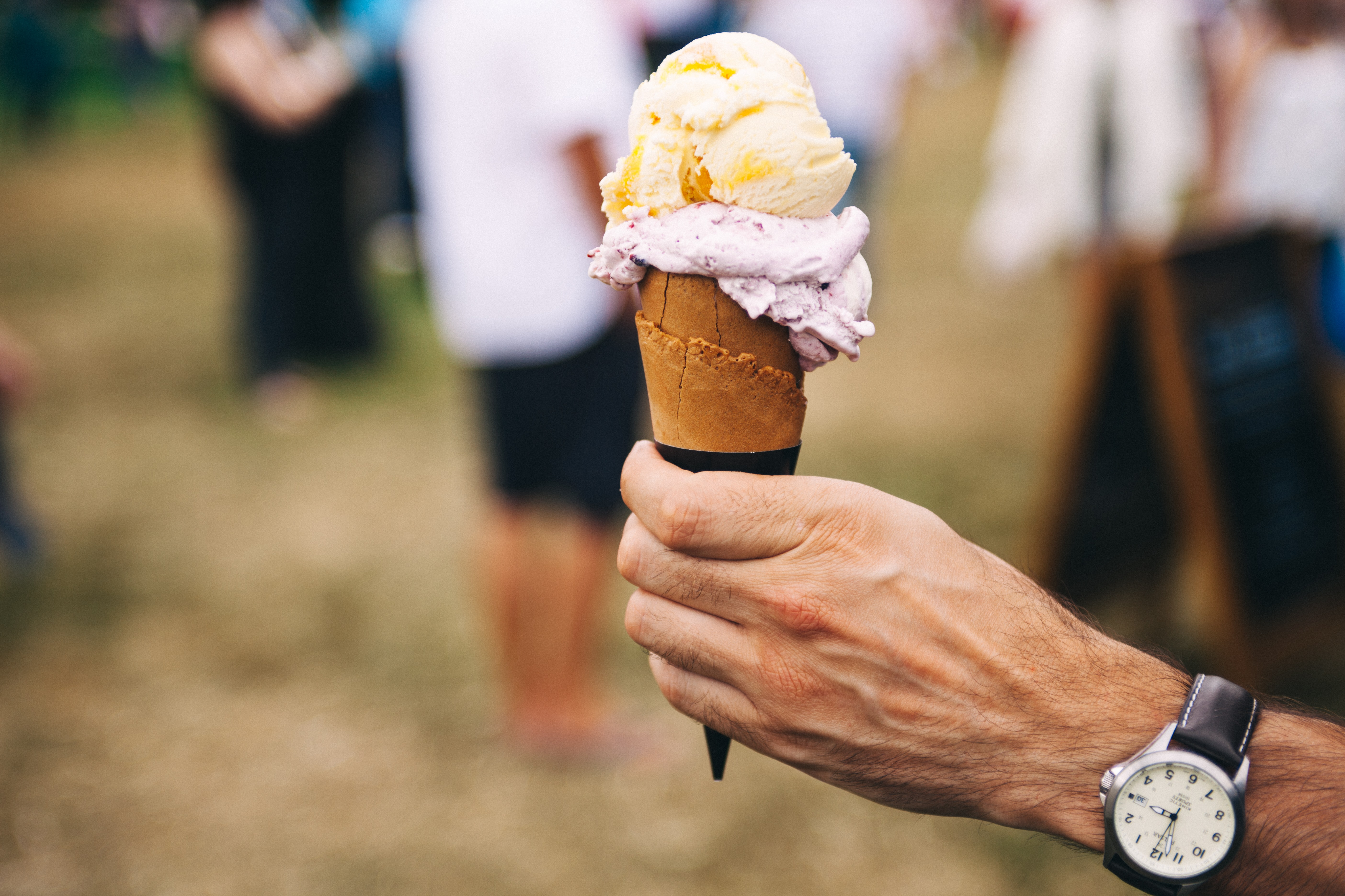 Hand hold an ice cream cone with two scoops at a festival