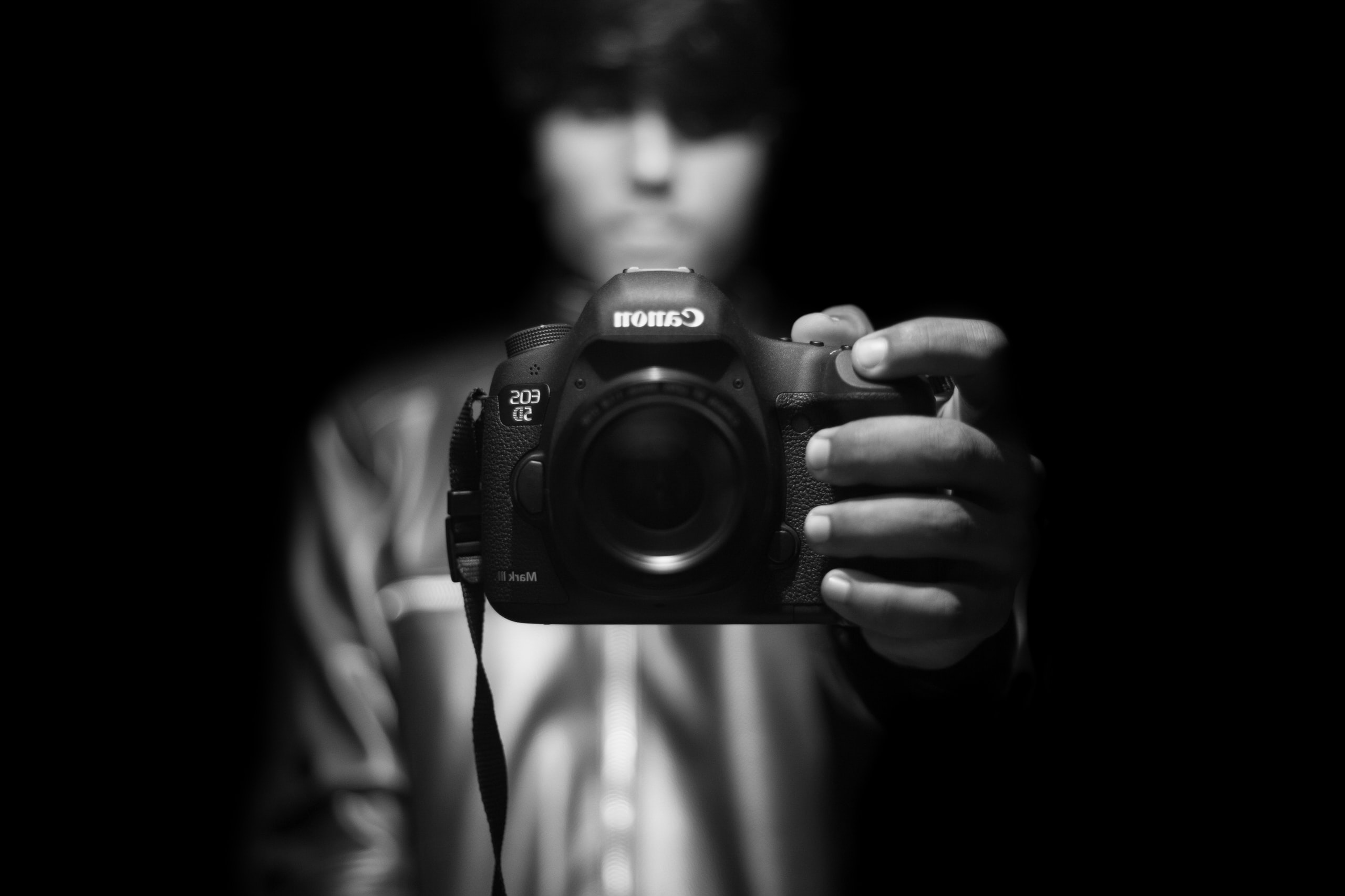A black-and-white shot of a man holding a Canon camera in front of them
