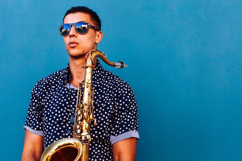 man holding saxophone instrument