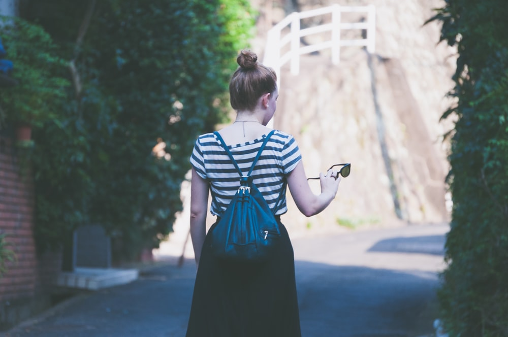 woman in striped shirt with backpack holding sunglasses while walking on street
