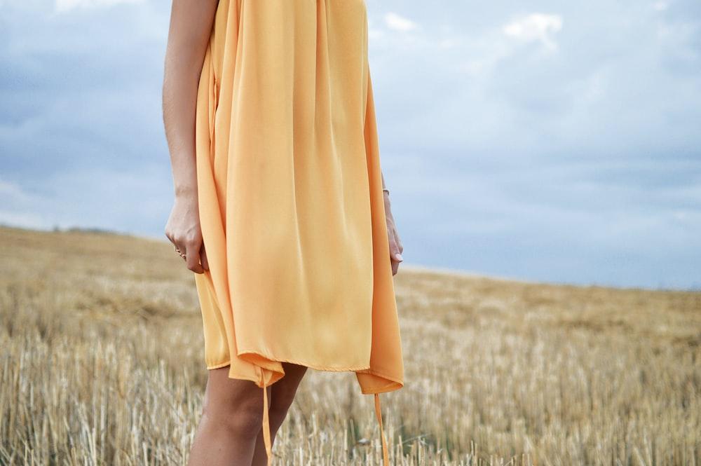 woman wearing yellow dress standing on green grass field