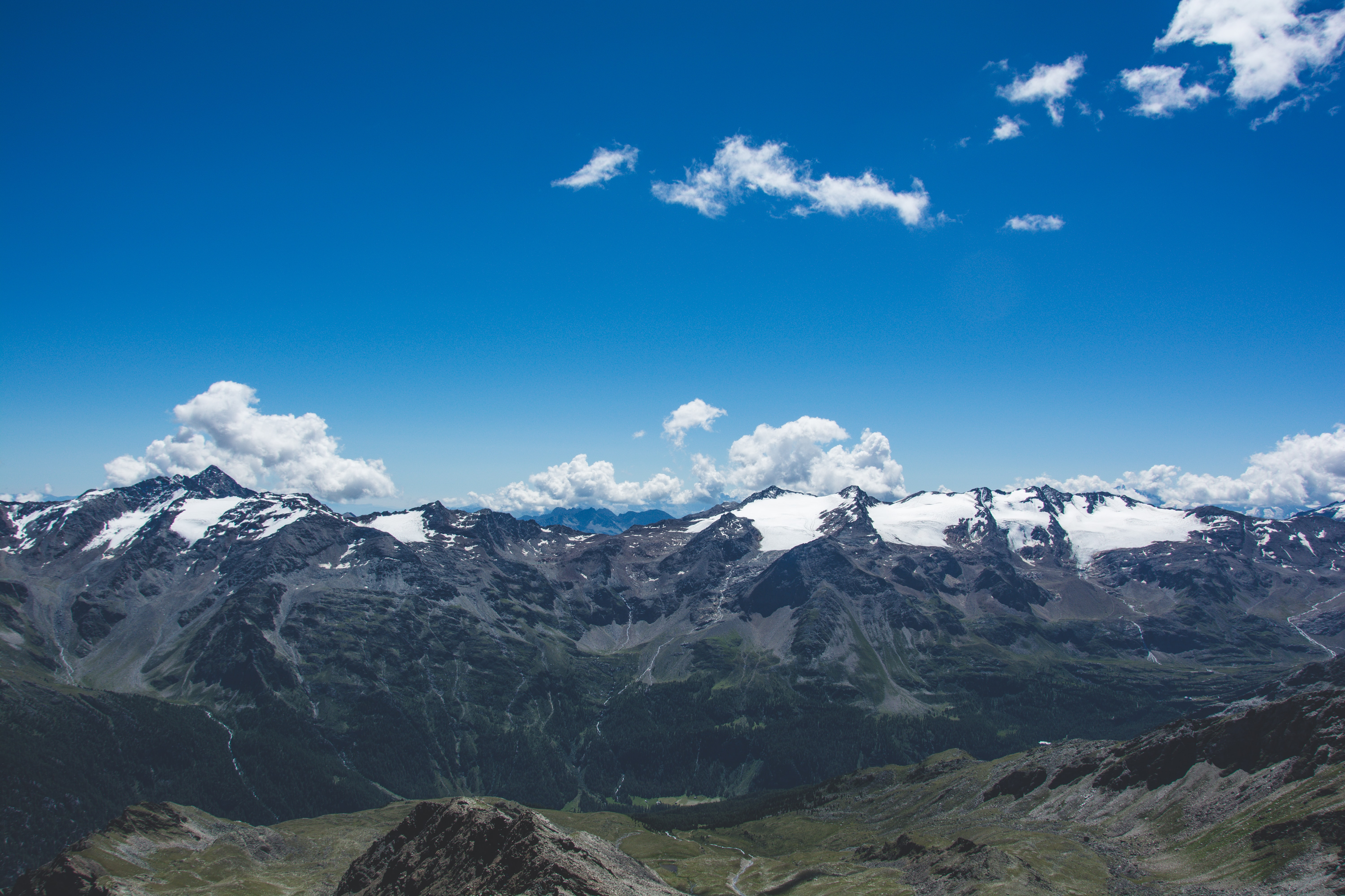 Snow-capped mountains under a blue sky with scattered clouds