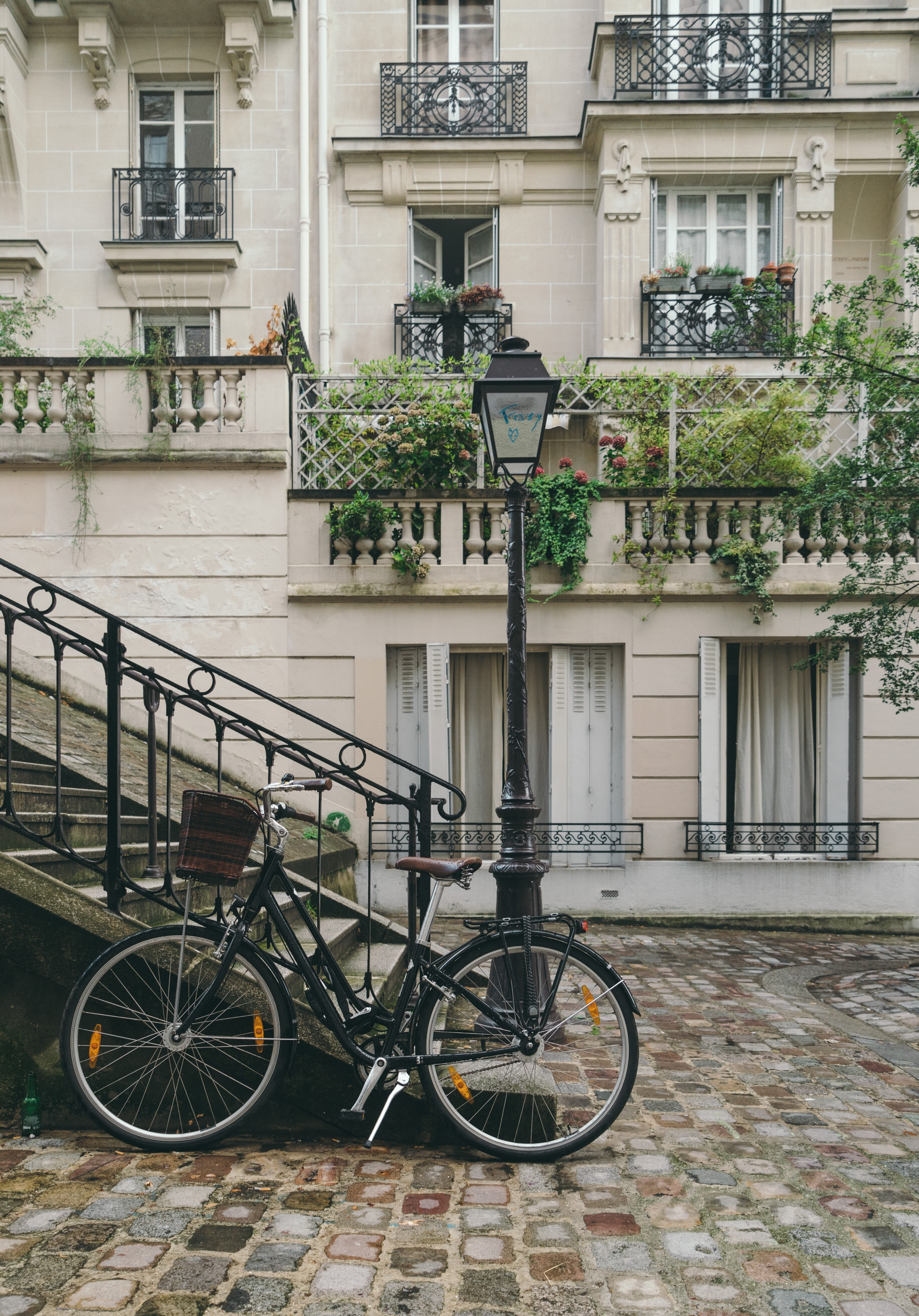 A bicycle resting against a flight of stairs and a lamppost with French buildings in the background.