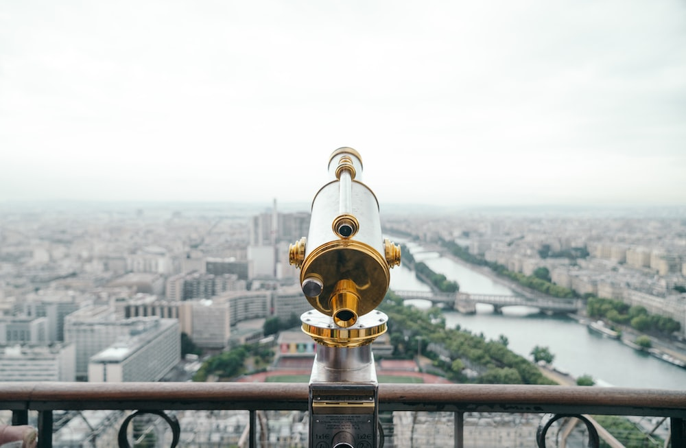 A telescope in front of a rail overlooking Paris and the Seine River