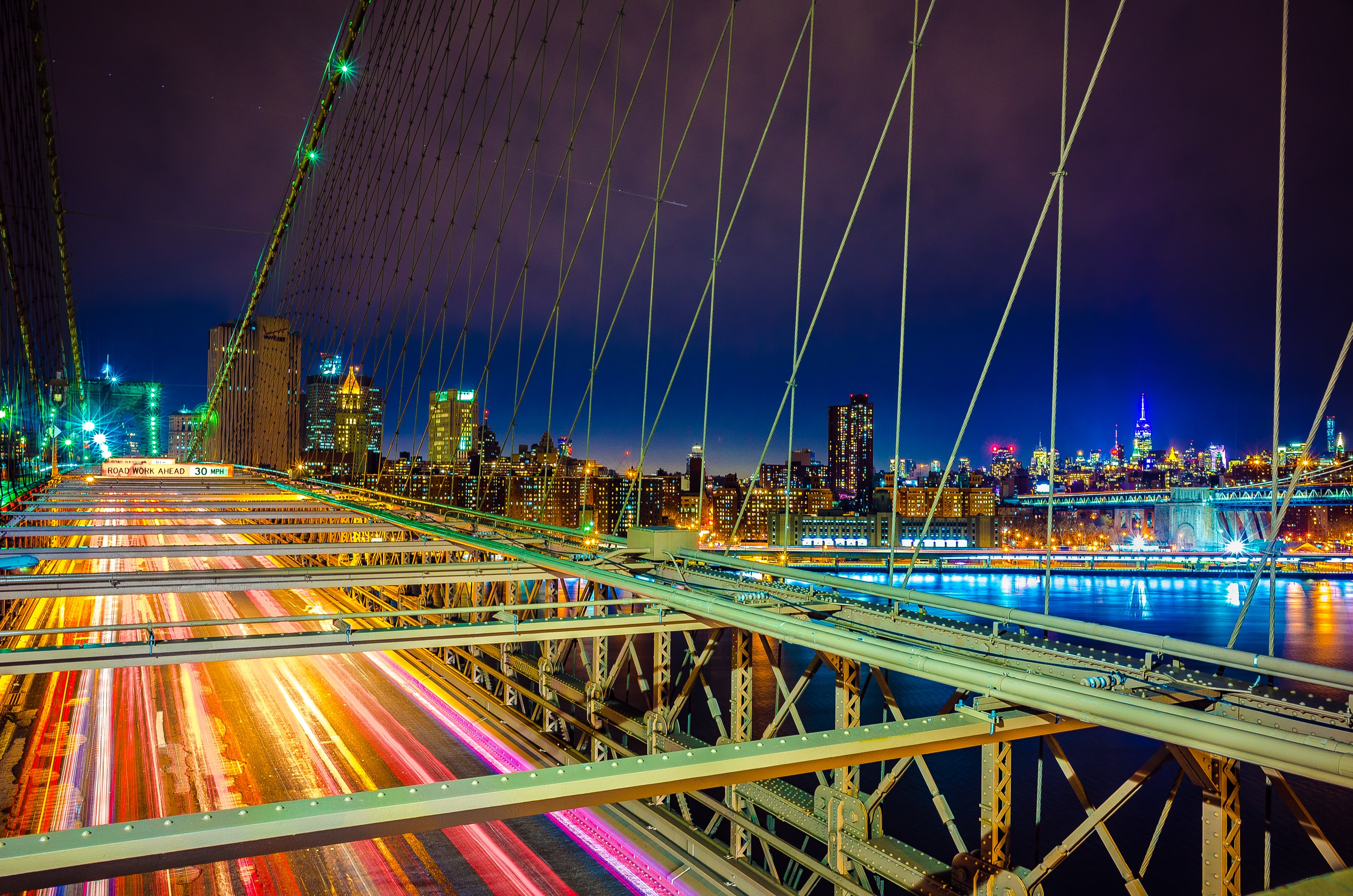 Cars light up the Brooklyn Bridge as they speed across it at night