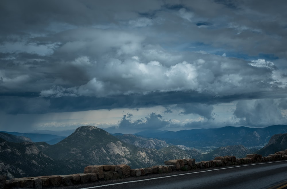 gray rocky mountains under cloudy sky during daytime