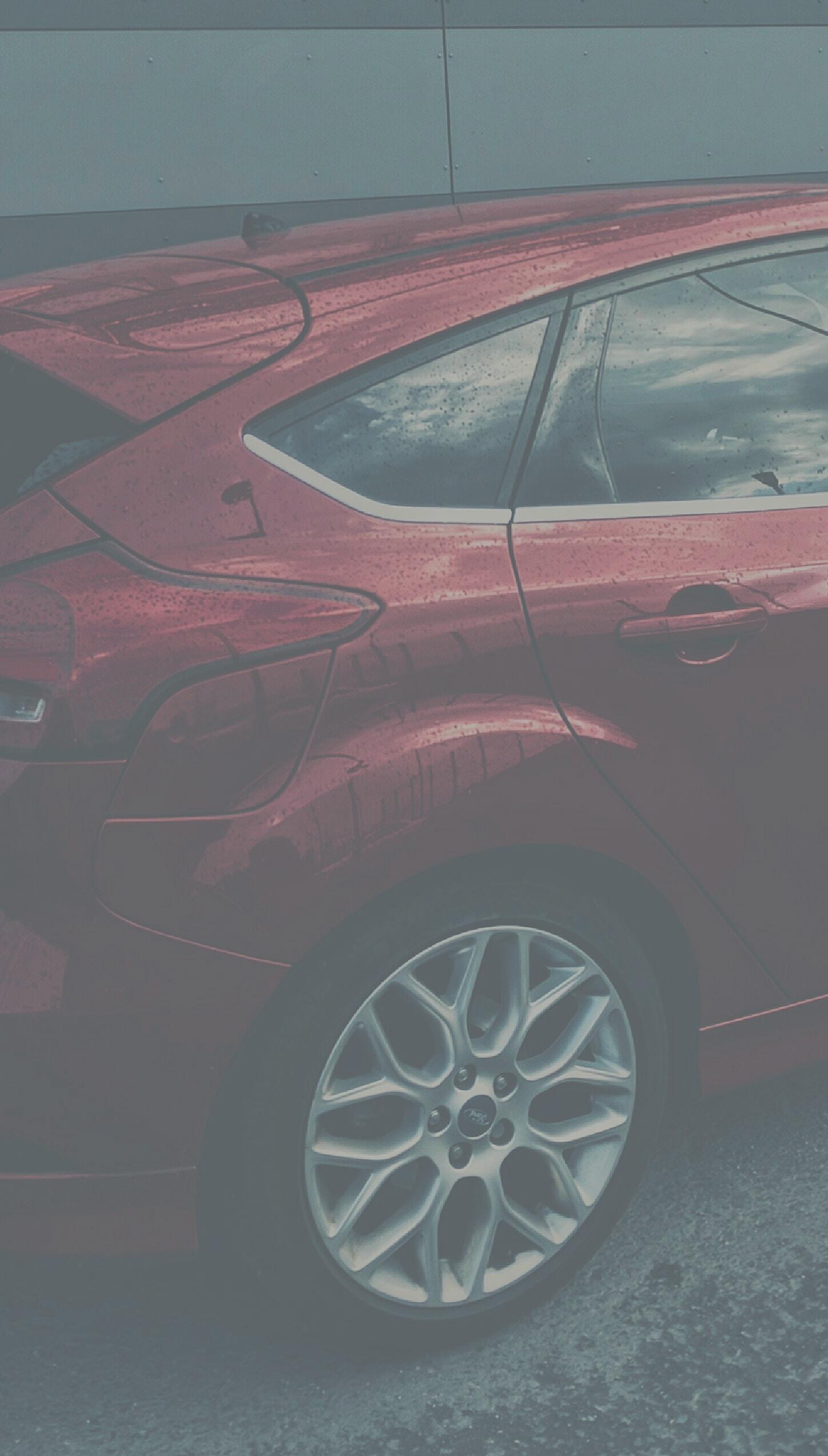 A red hatchback parked.