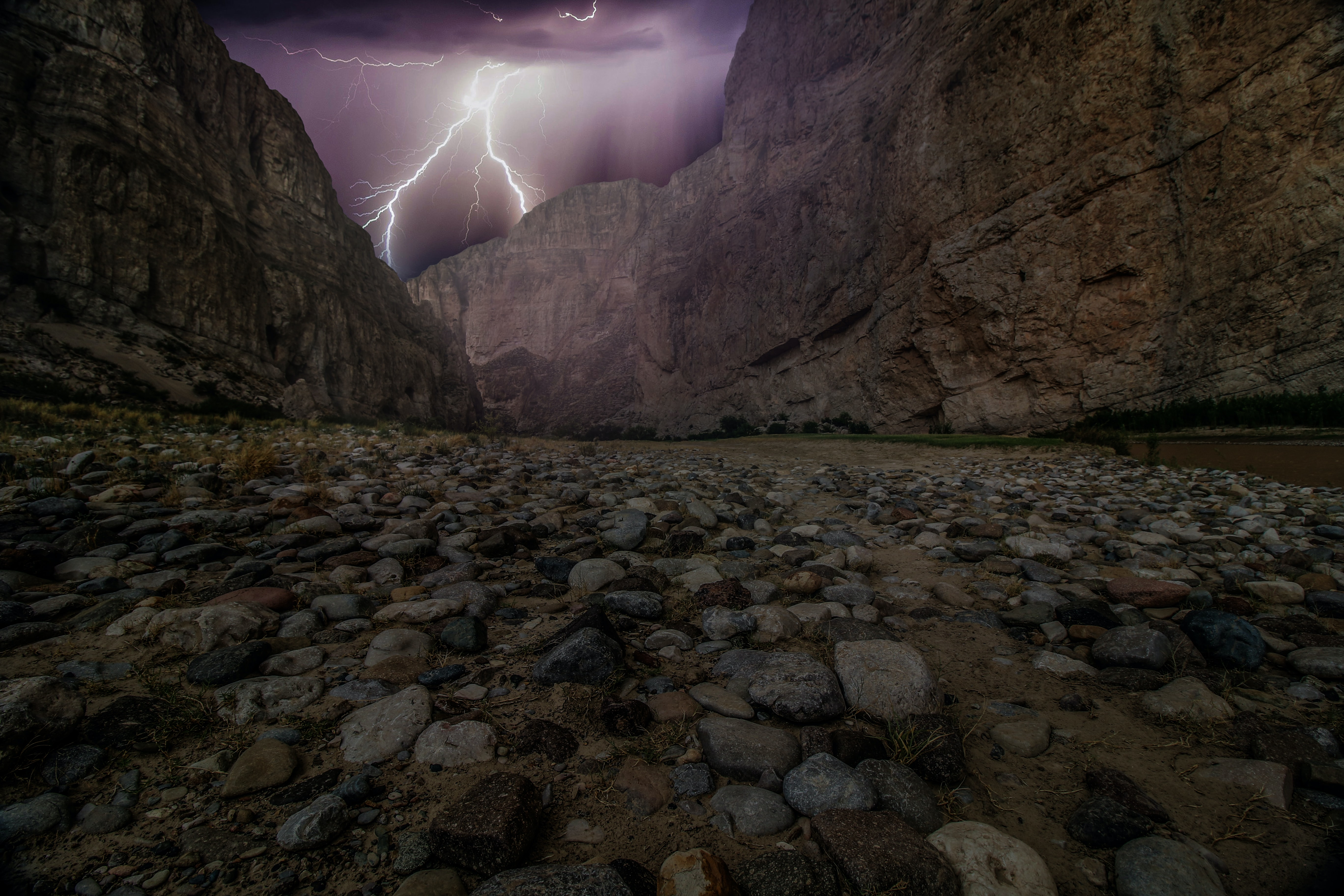 Bolt of lightning seen behind the rocky Boquillas Canyon during a storm