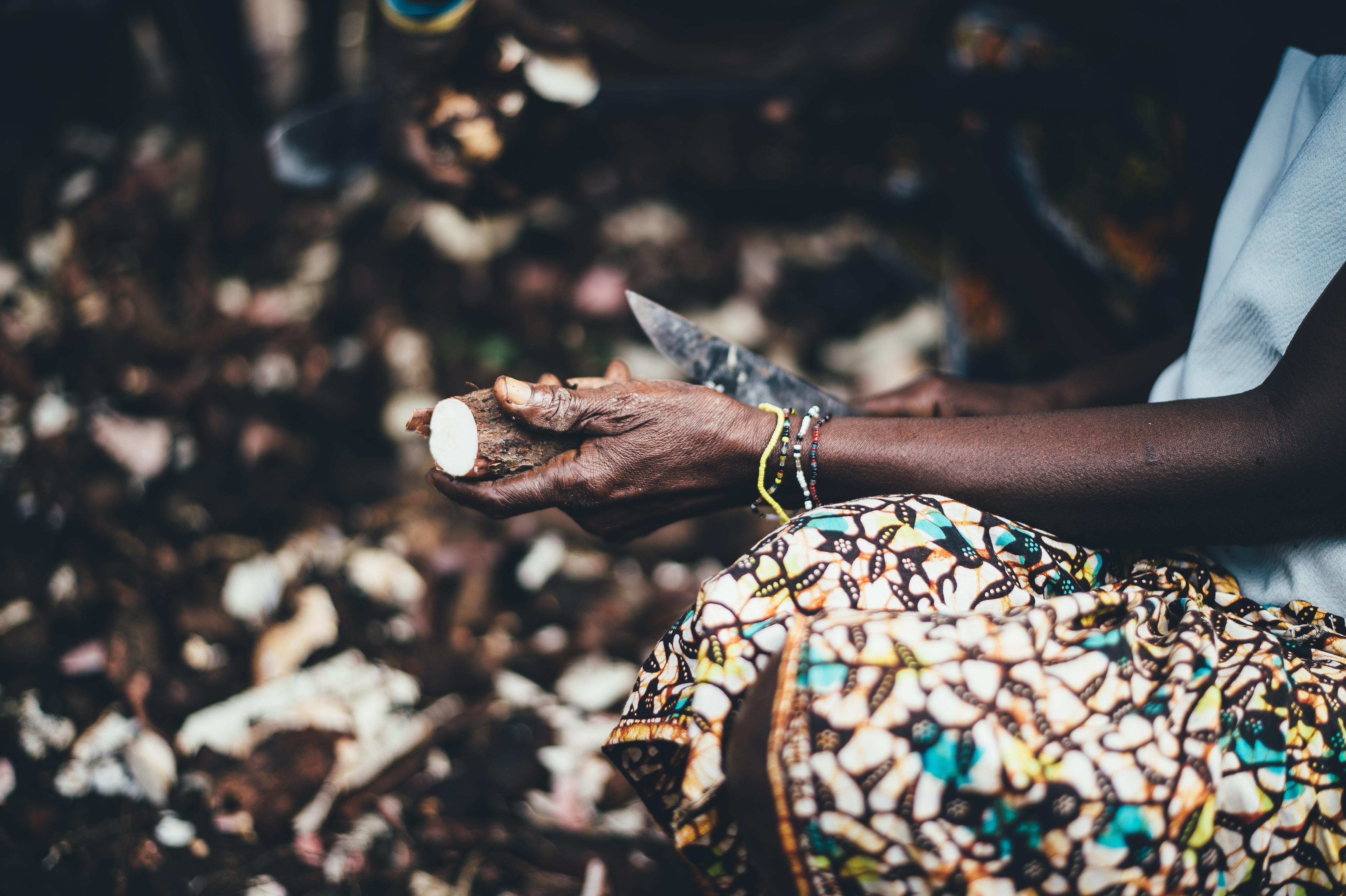 A woman wearing a patterned shirt, peeling food in Sierra Leone