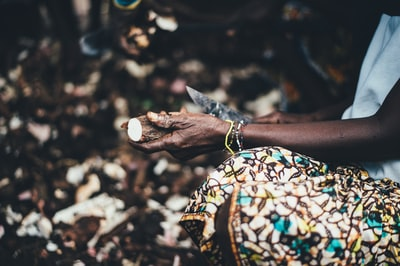 person carving wood using knife sierra leone teams background