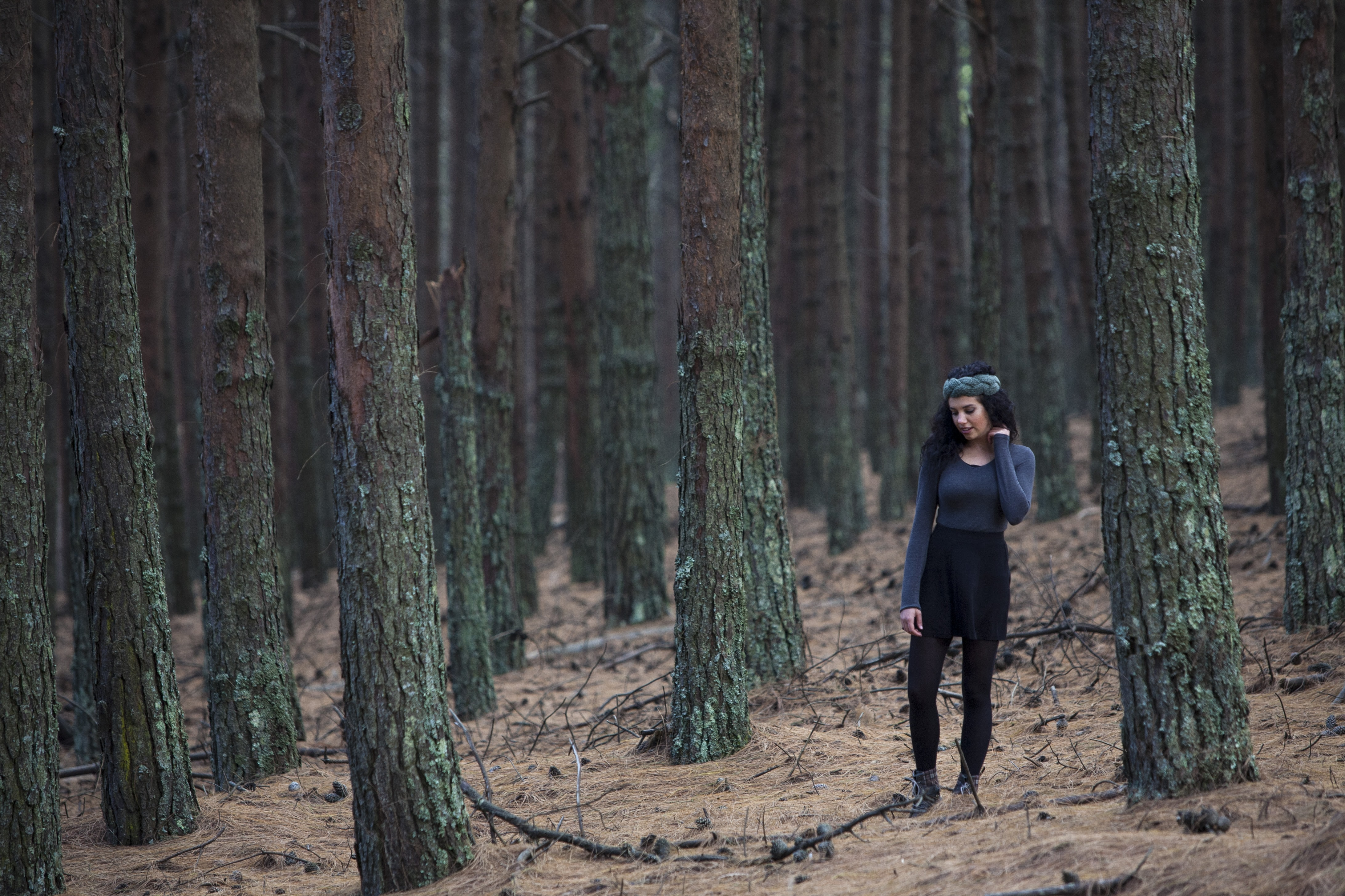 A young woman walks on the needle-covered floor of a pine forest