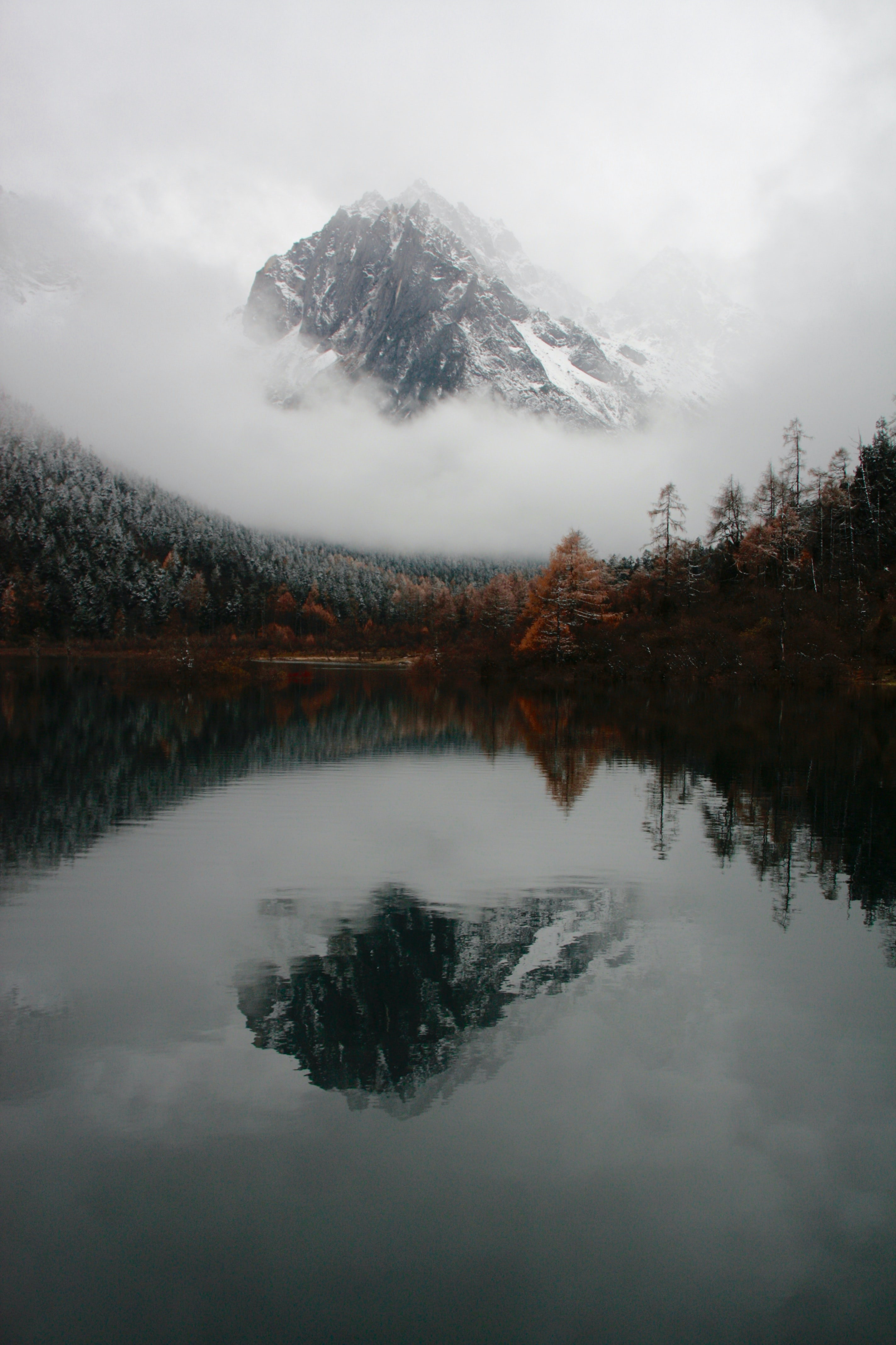 Mountain peak reflects in calm waters surrounded by autumnal trees