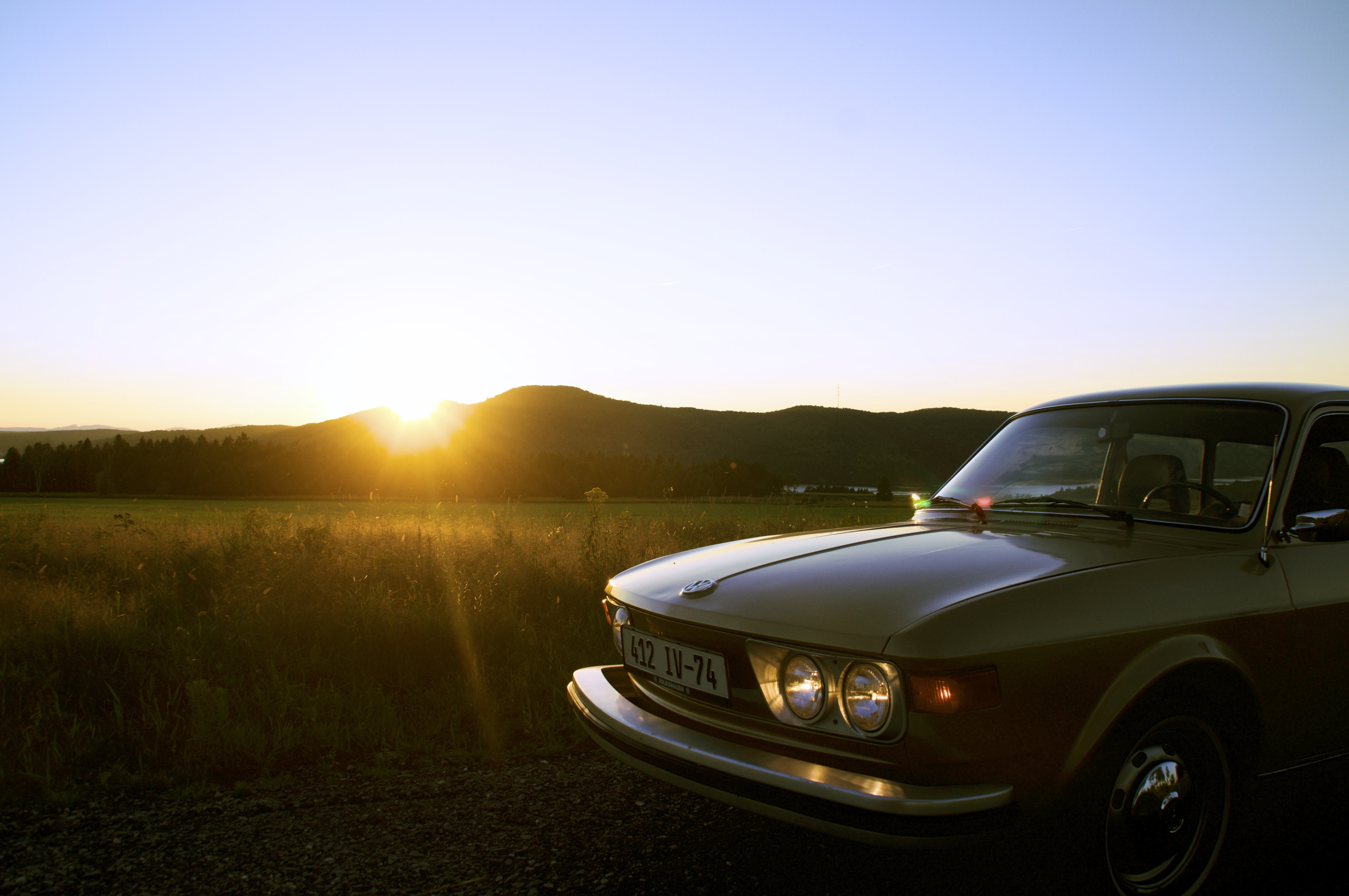 Vintage car parked near a field at sunset