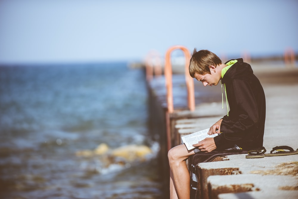 boy sitting on dock while reading
