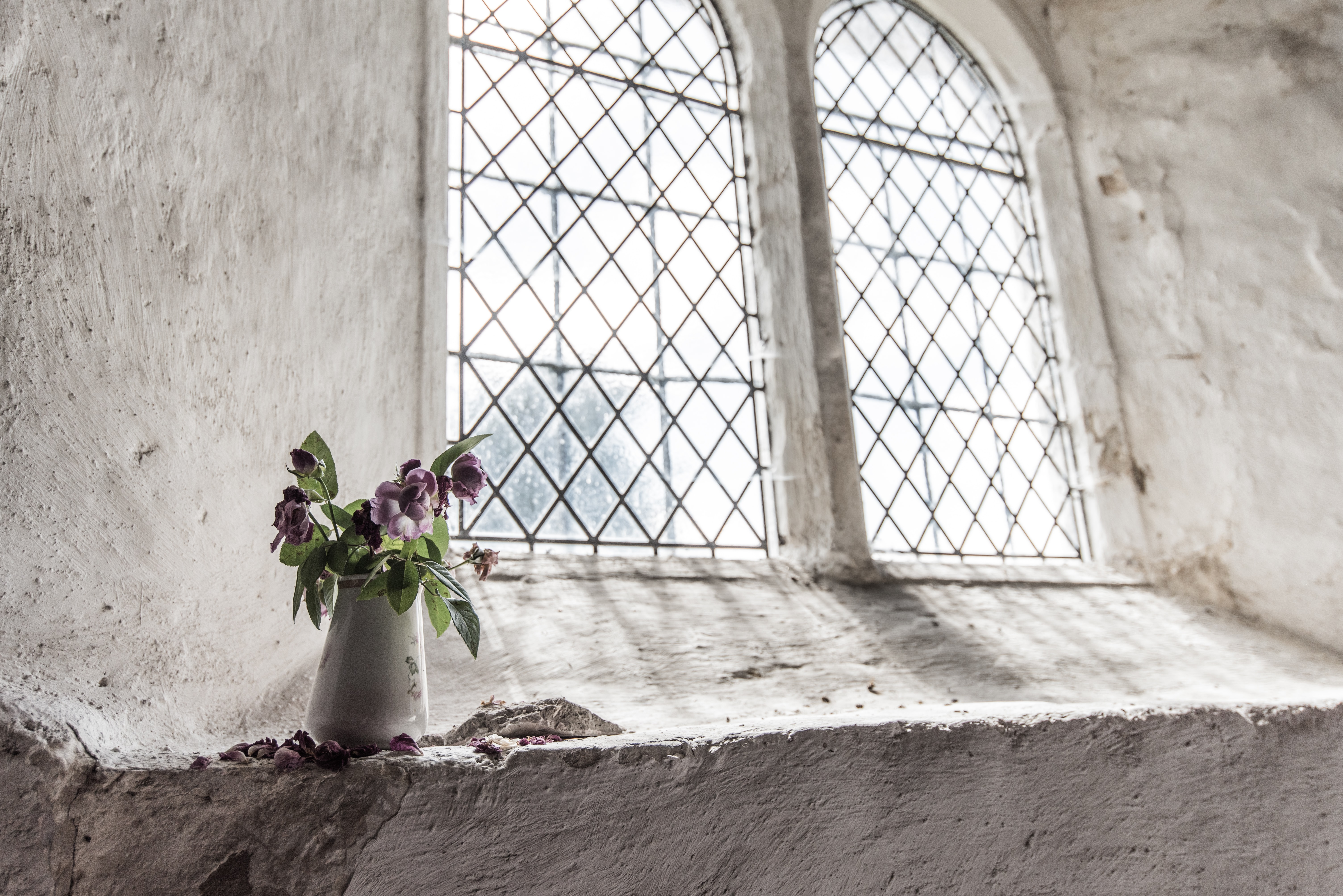 A white vase with purple flowers on a window ledge in an old building