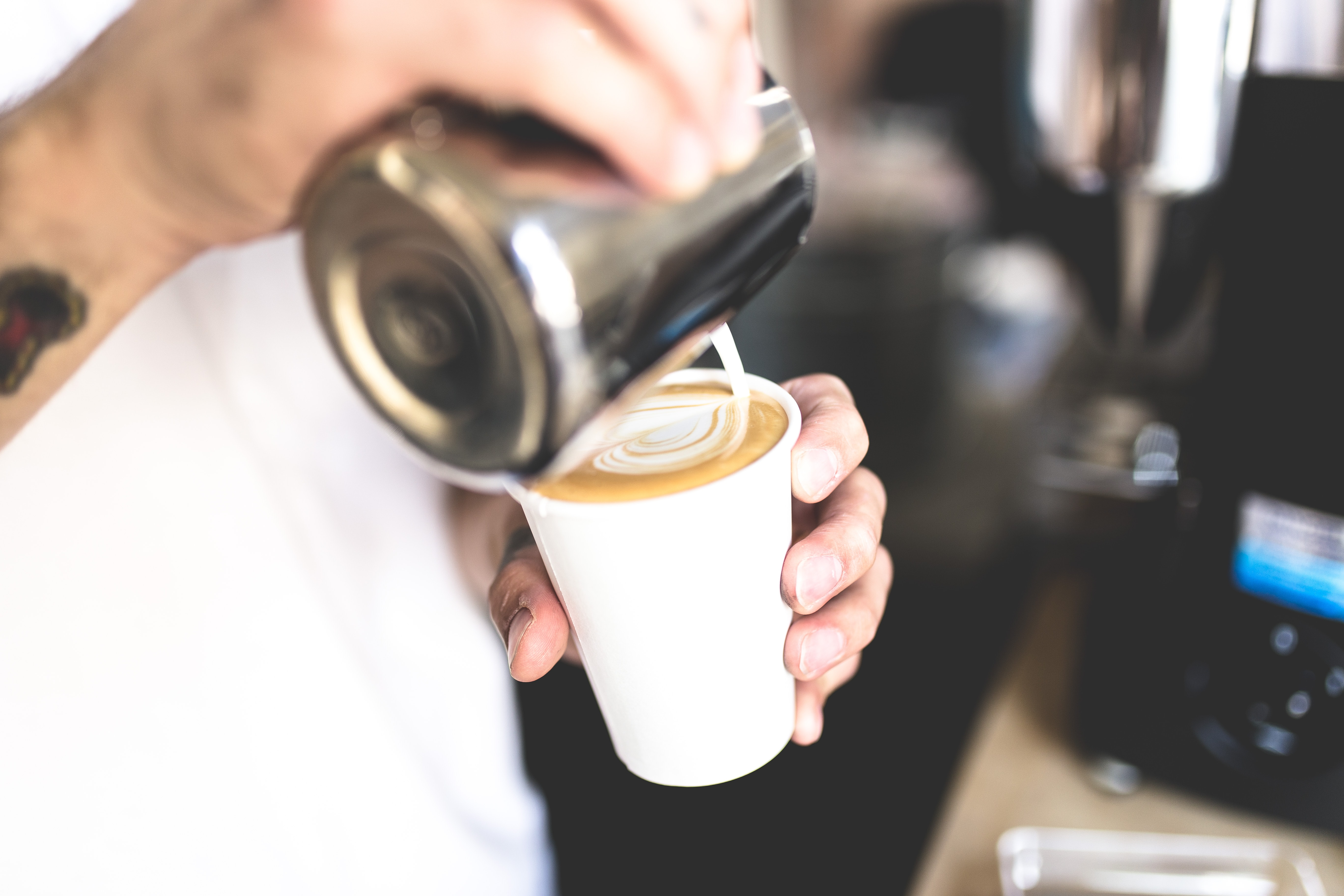 A barista pouring milk into a coffee cup