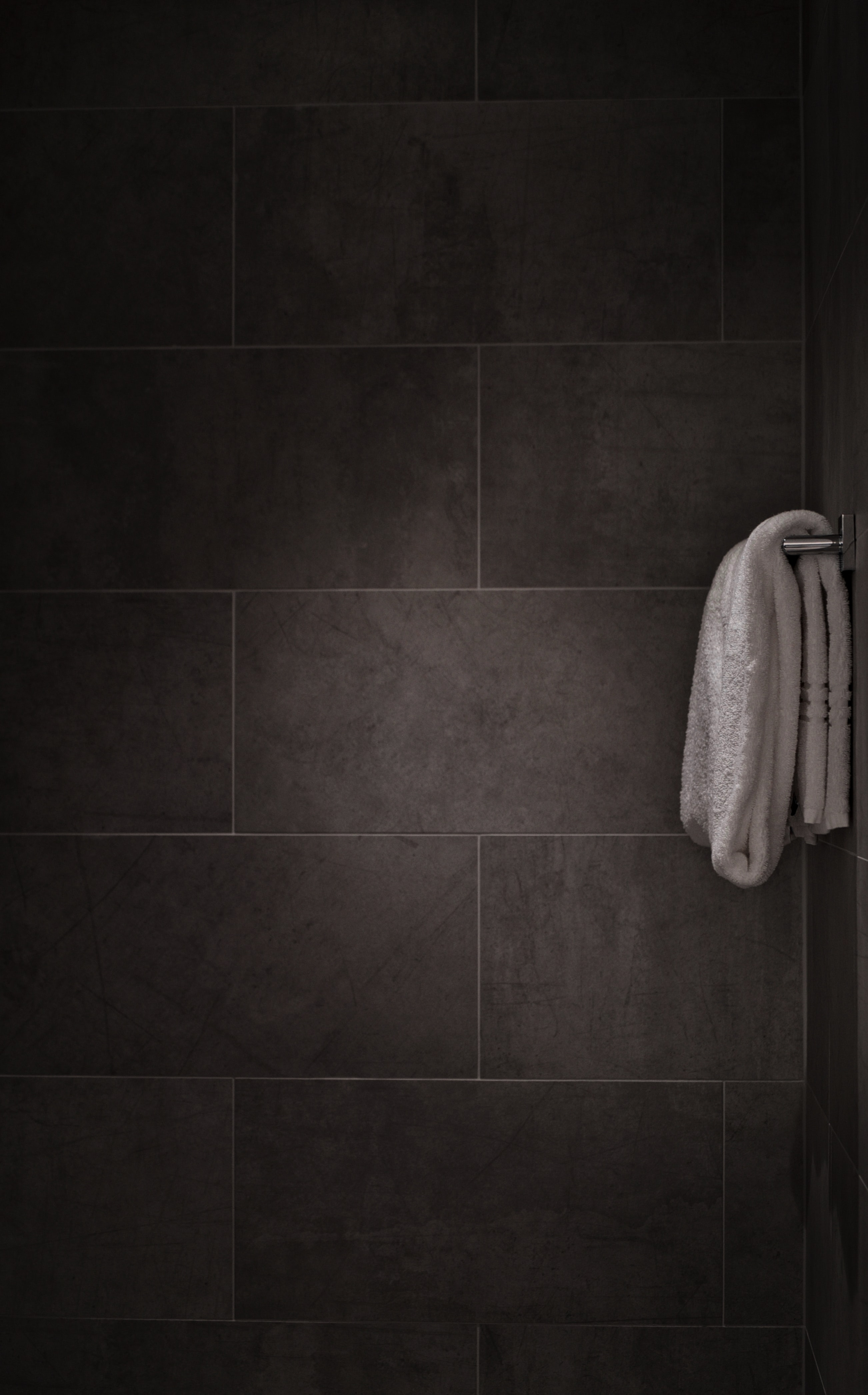 Black and white minimalist shot of white towel on rail in tiled bathroom