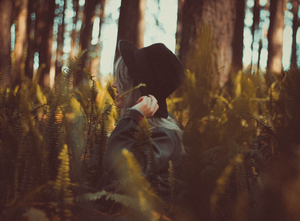 woman holding hat on forest at daytime