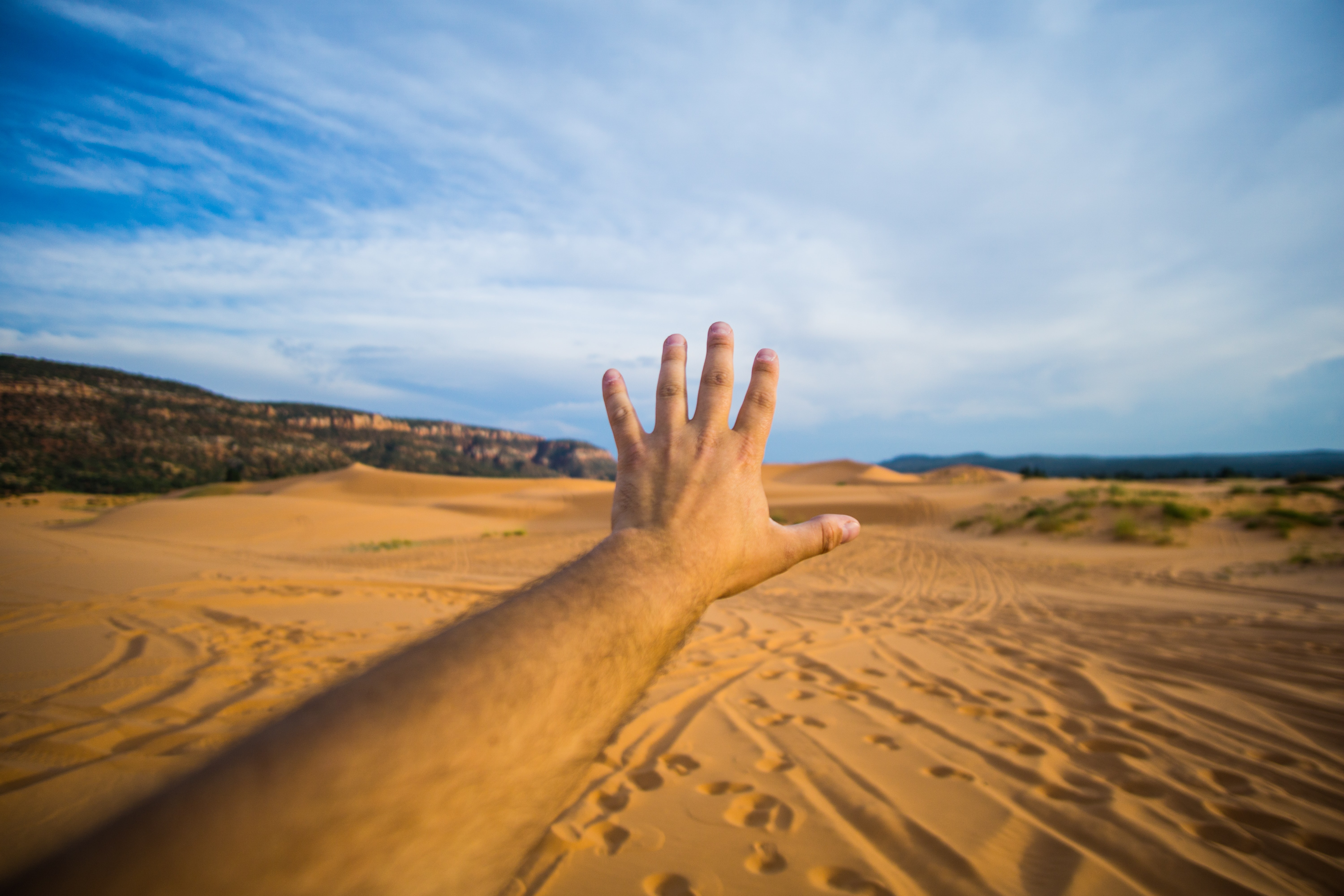 left human hand about to reach sand and sky