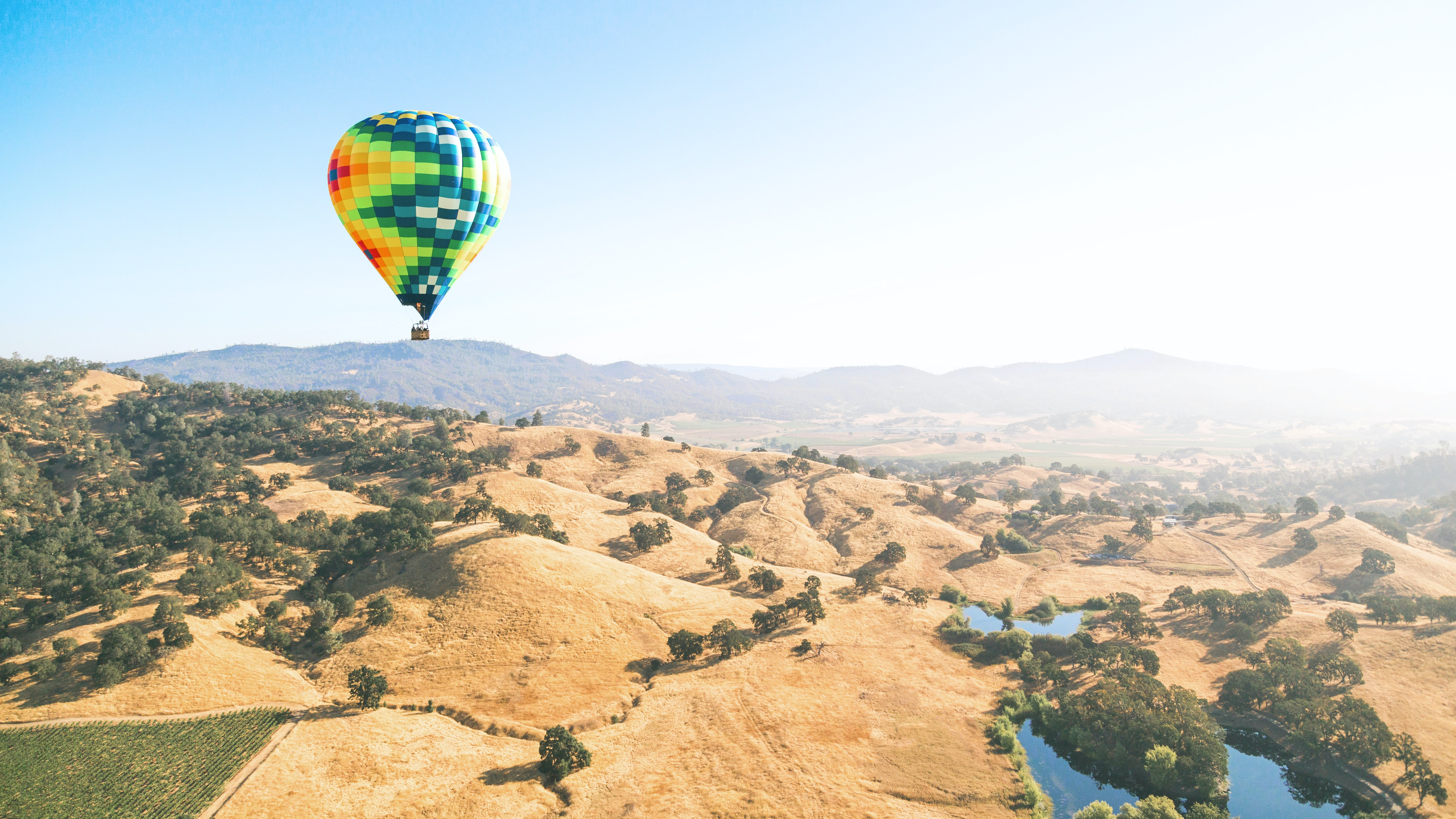 green and orange hot air balloon flying over the mountains