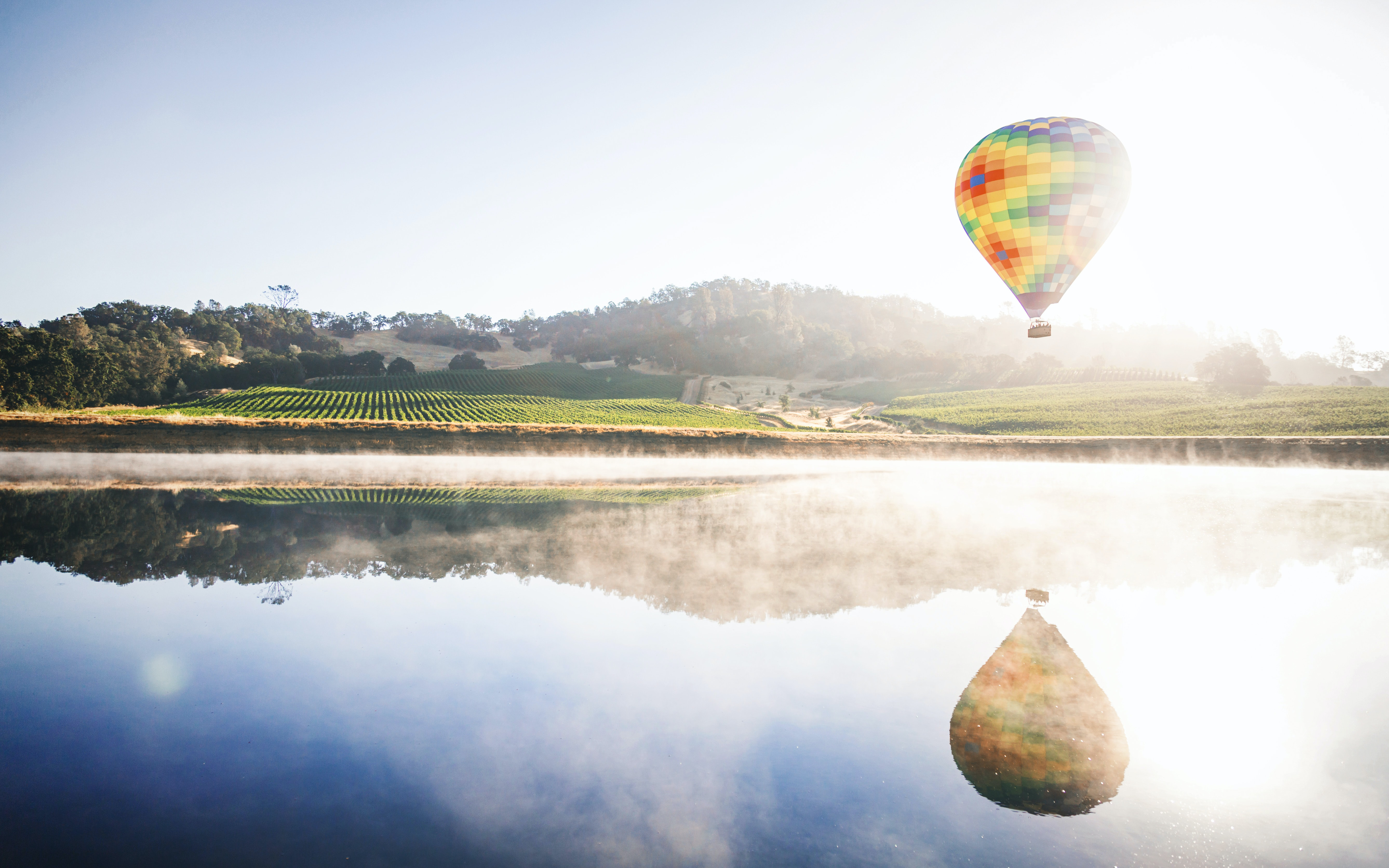 A hot air balloon flying over a lake on a foggy morning.