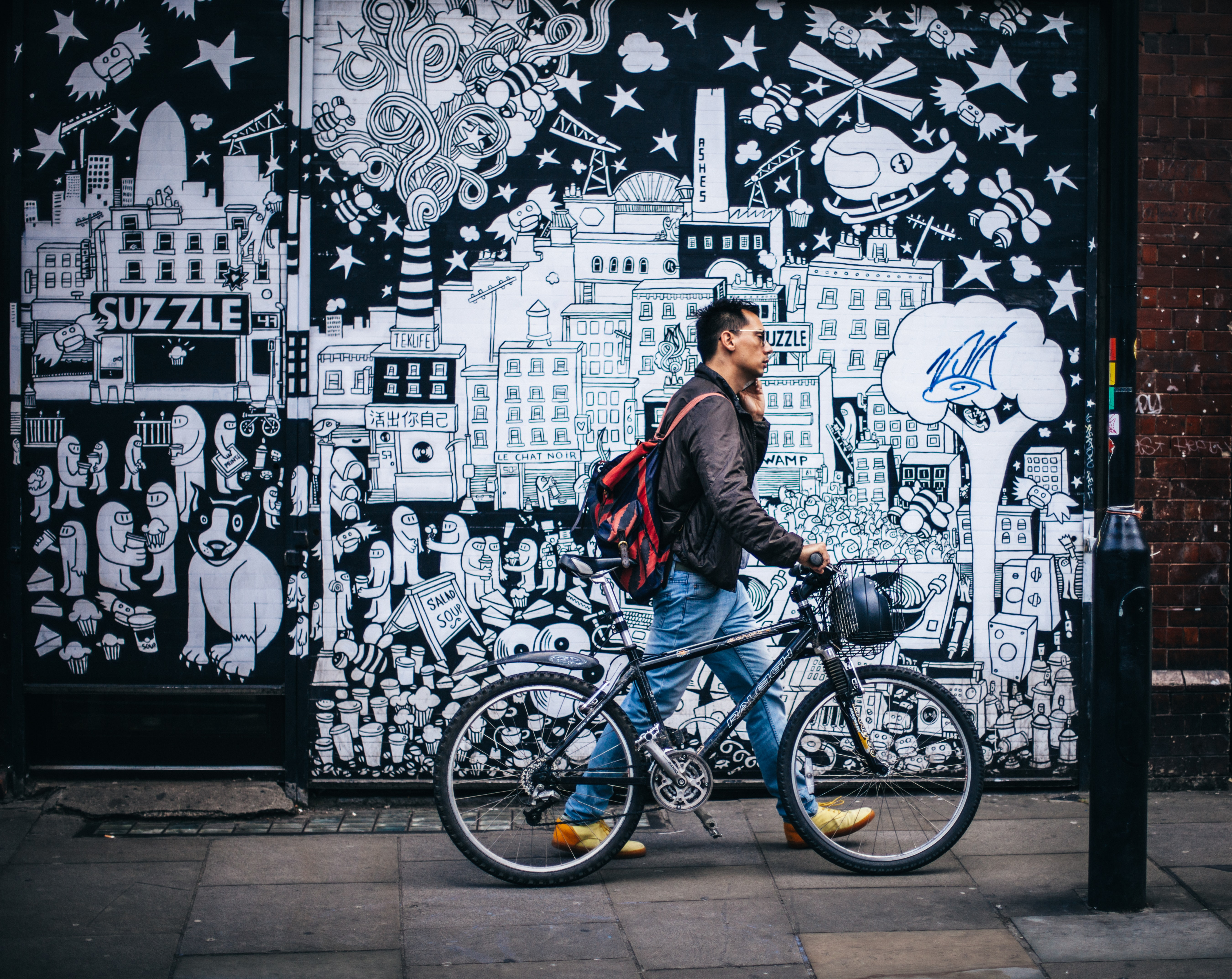 Man walking on sidewalk with bike past black and white cartoon graffiti mural at Brick Line